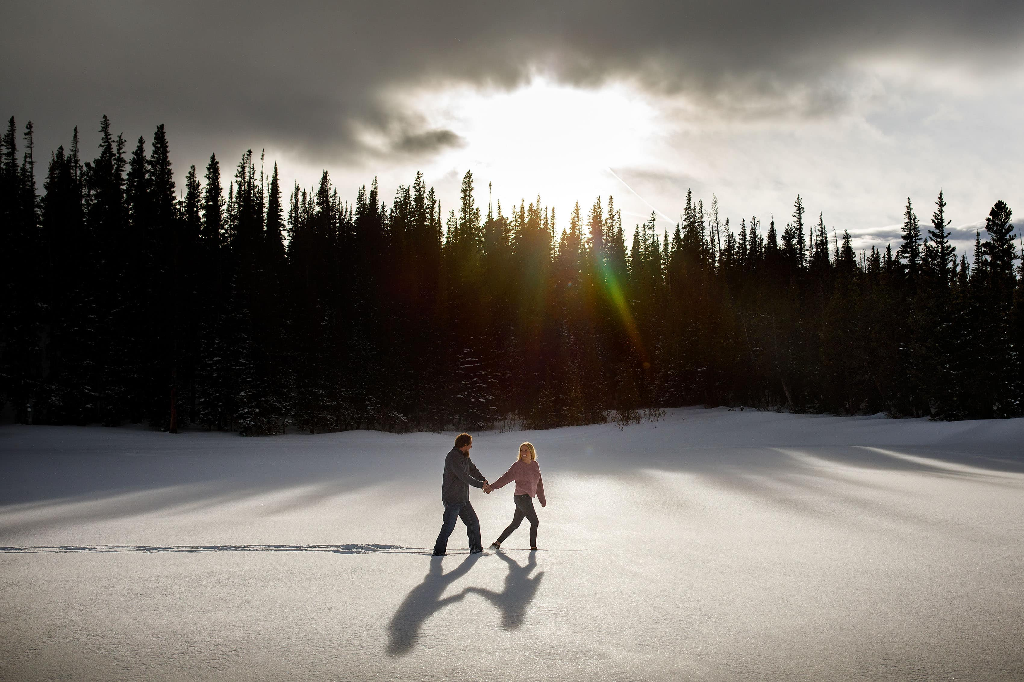 Meaghan and Aaron walk together on the snow covered ice during their winter Brainard Lake Engagement in Colorado