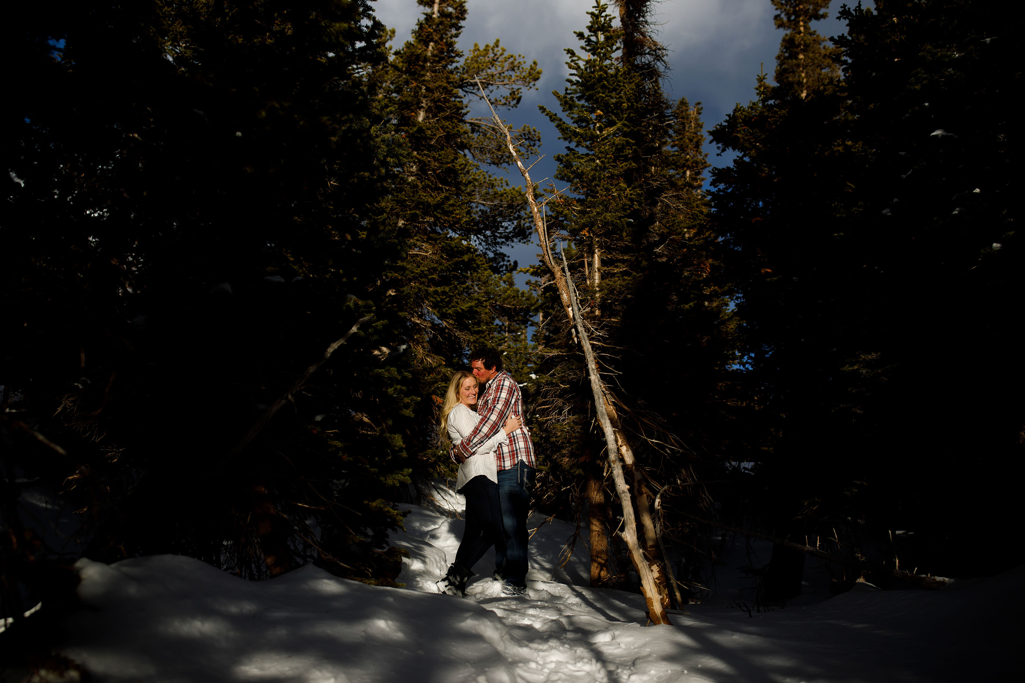 Aaron kisses Meaghan in the trees at Brainard Lake during their winter engagement session in Colorado