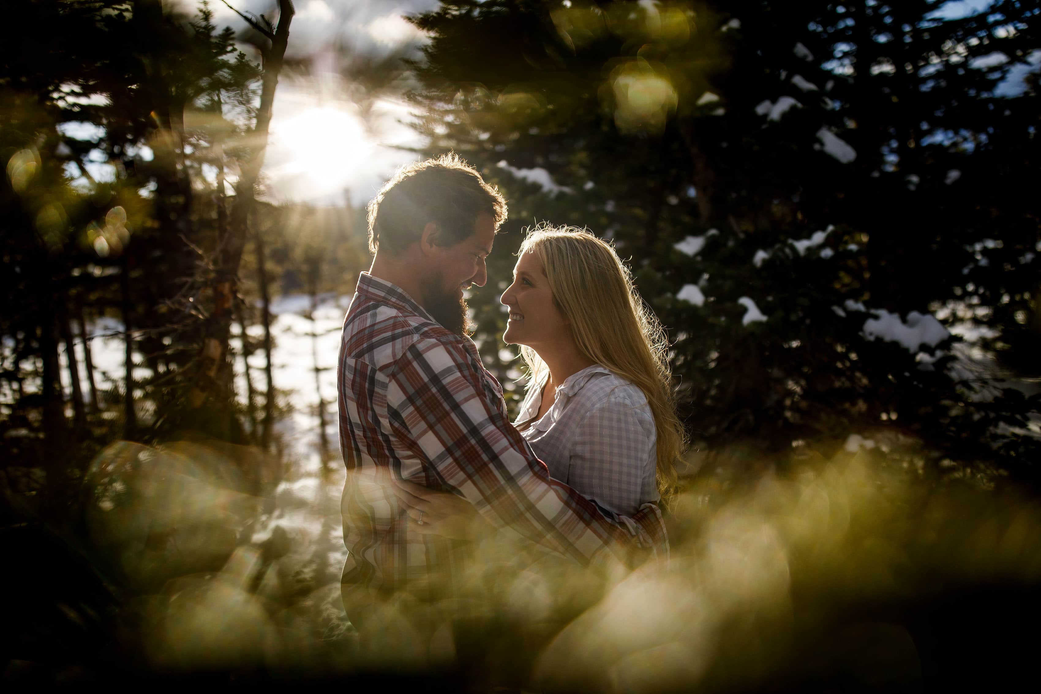 The light shines through the trees as Meaghan and Aaron pose together at Brainard Lake
