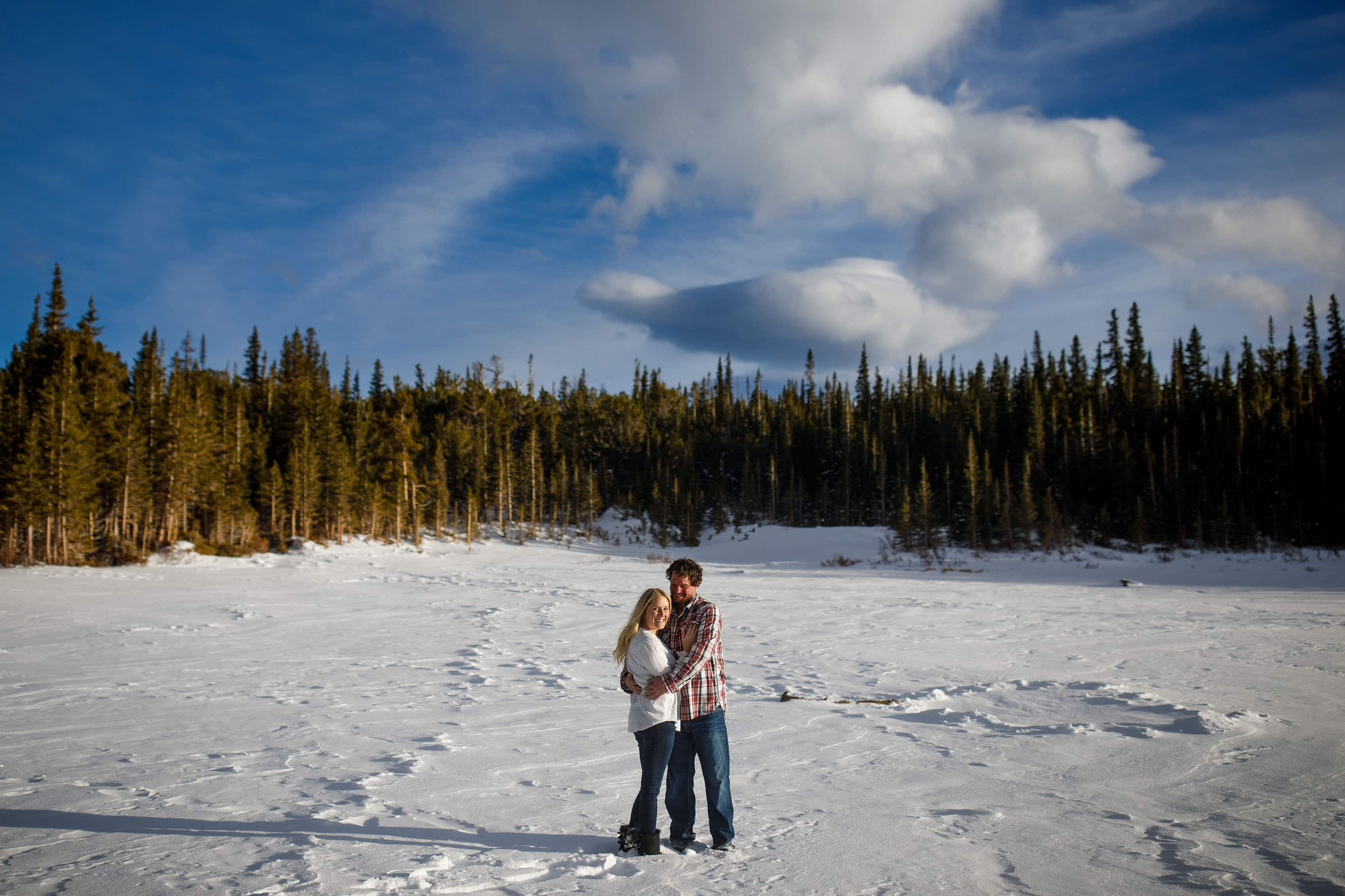 Meaghan smiles while Aaron keeps her wam while they stand on snow covered Brainard Lake during their engagement session near Ward, Colorado