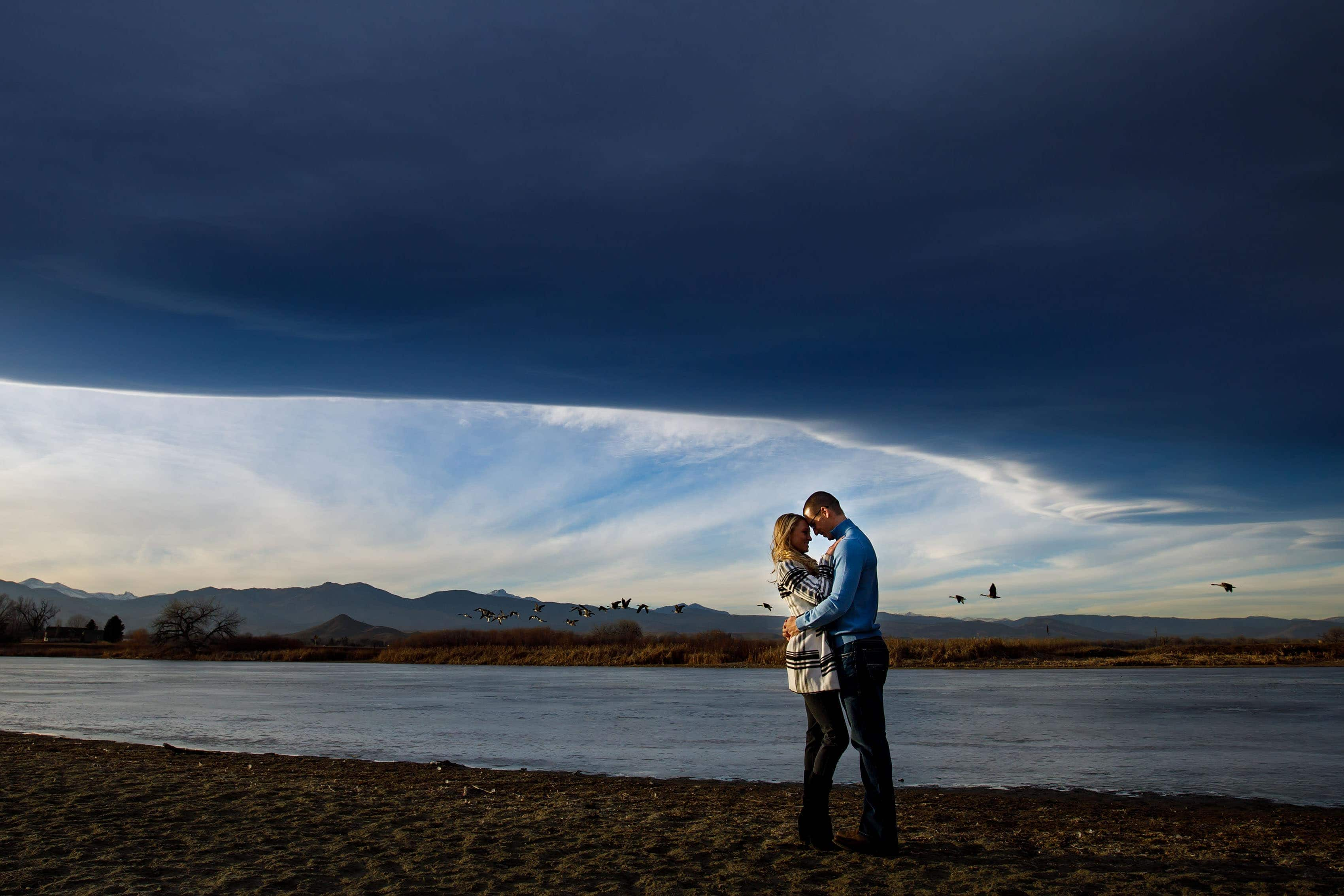 Kinsey and Sam stand near Dodd Reservoir in Boulder County as geese fly by during their engagement photos
