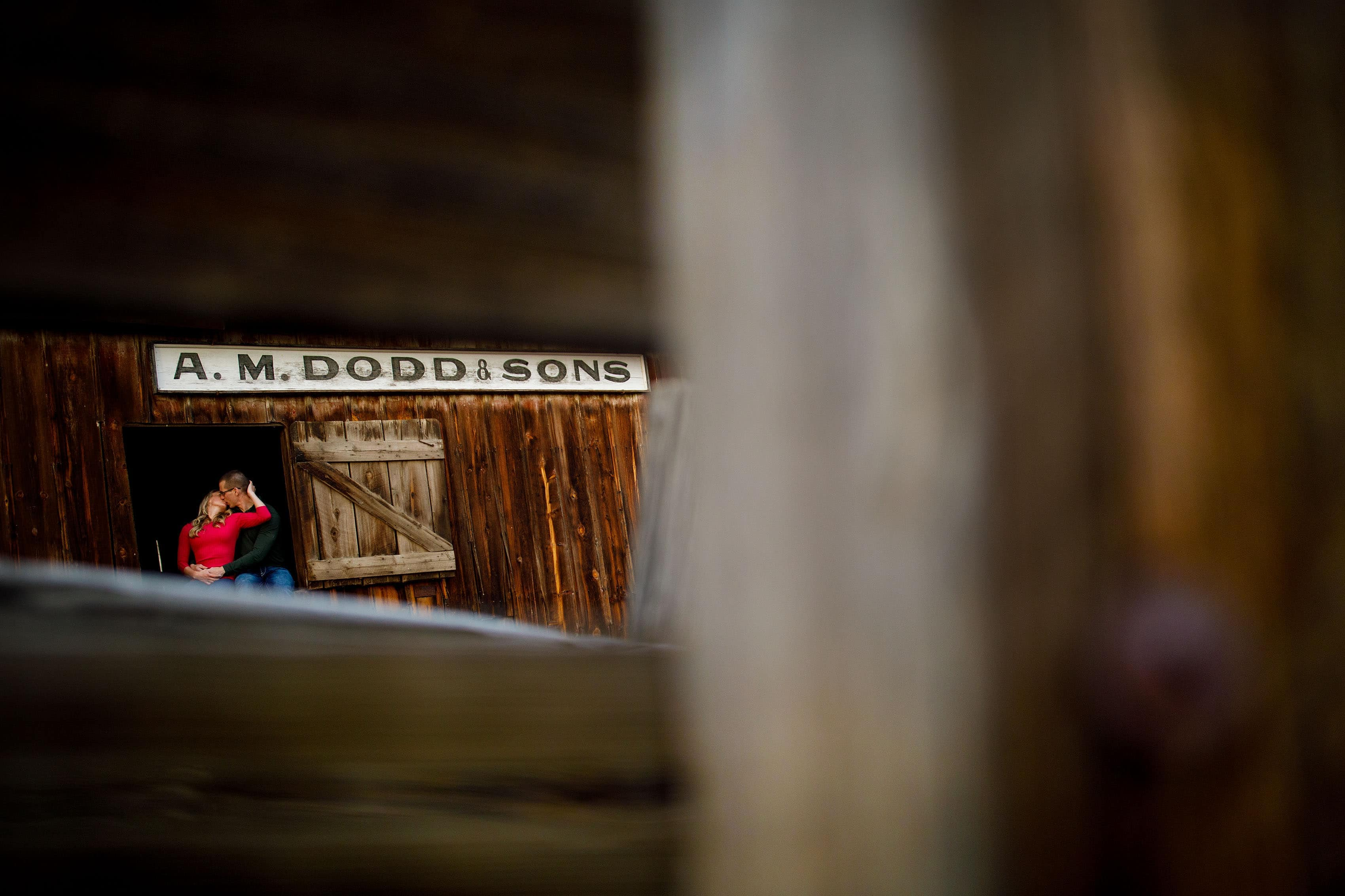 Kinsey and Sam share a kiss while sitting in the A.M. Dodd & Sons barn during their rustic barn engagement