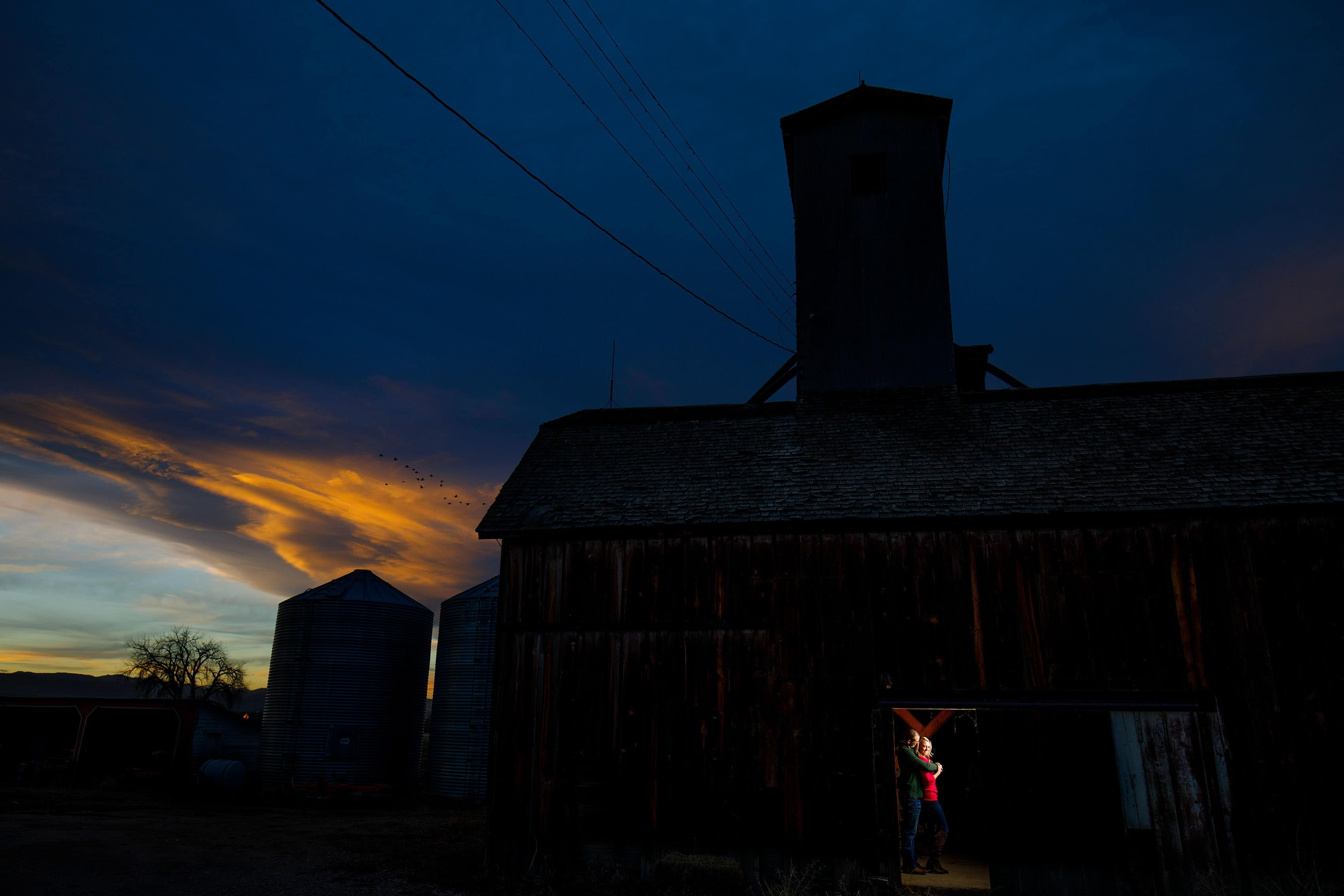 The sun sets behnd the farm during Kinsey and Sam's rustic barn engagement session near Boulder, Colorado