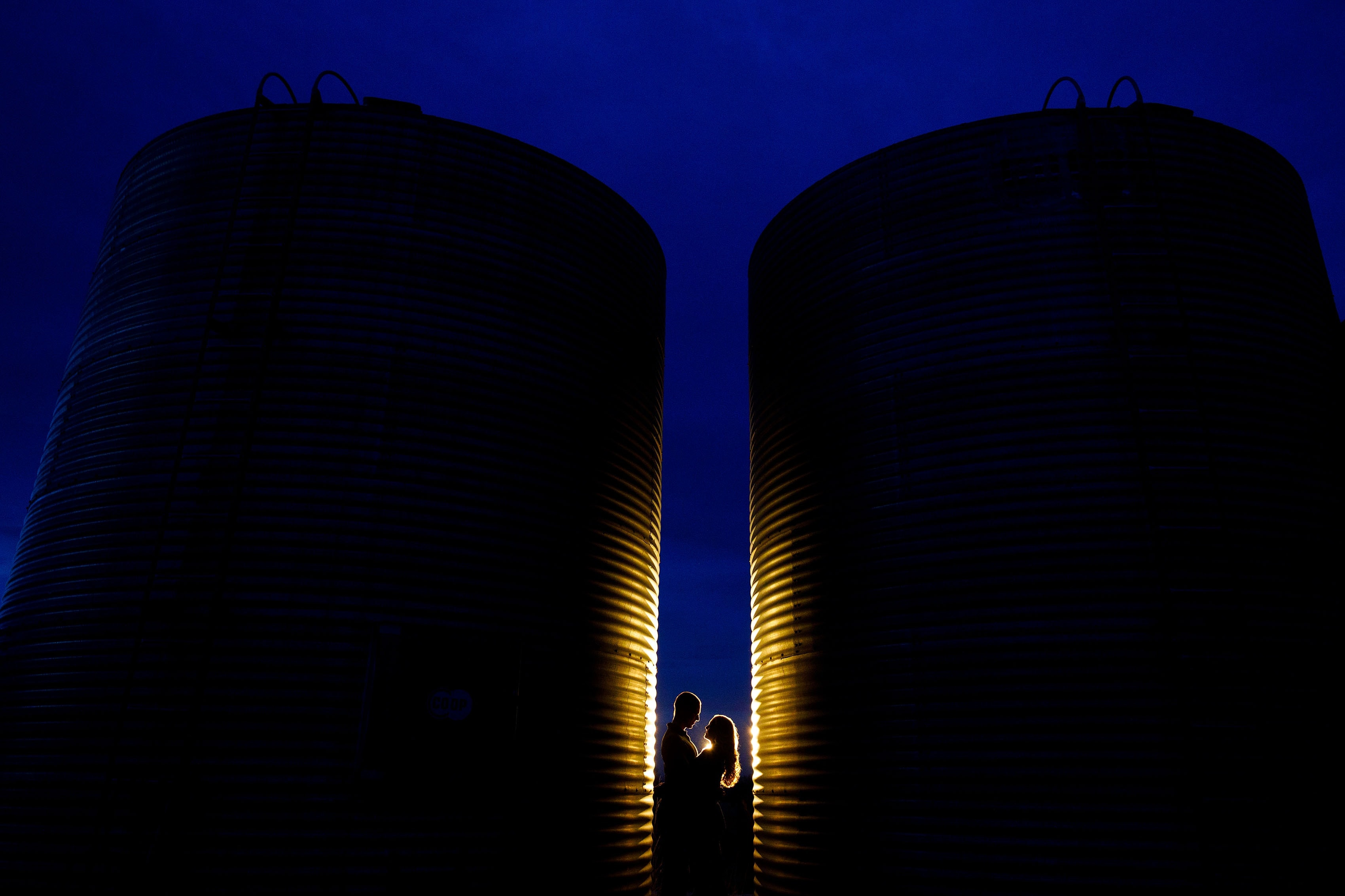 Kinsey and Sam pose together between a pair of silos on a farm in Boulder, Colorado