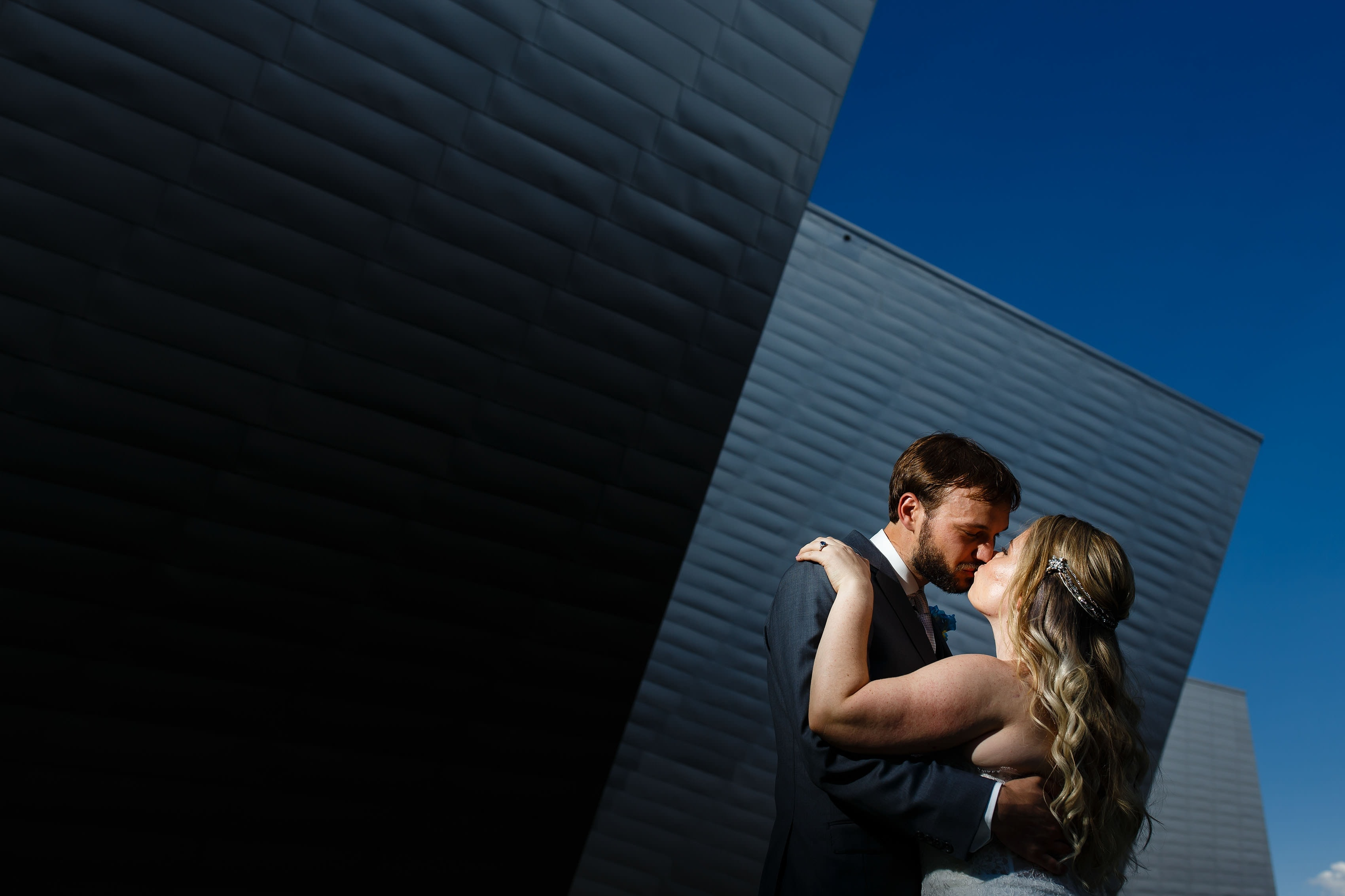 A couple kisses outside the Denver Art Museum on their wedding day