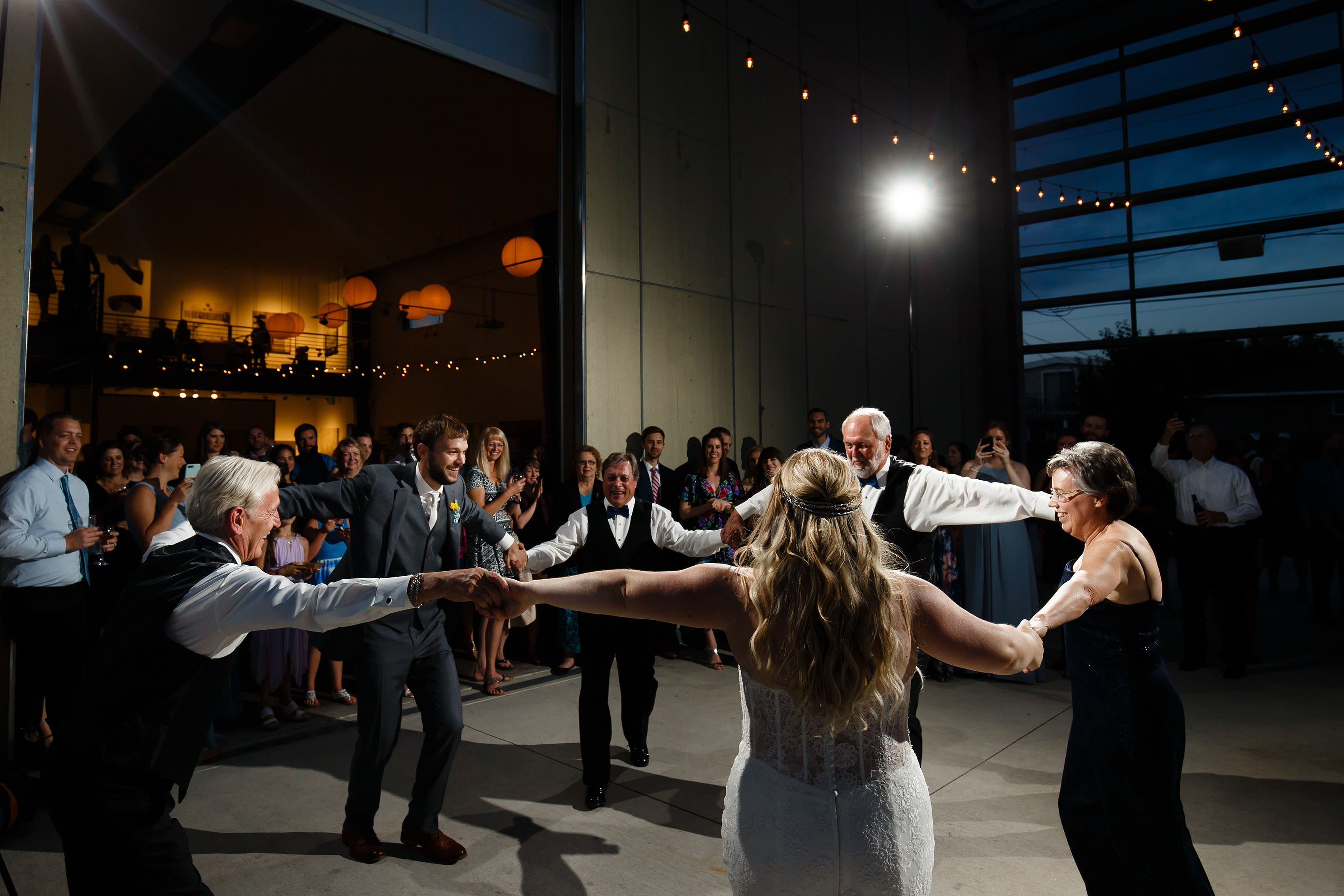 The bride and groom dance with their family on the patio during their Space Gallery Wedding