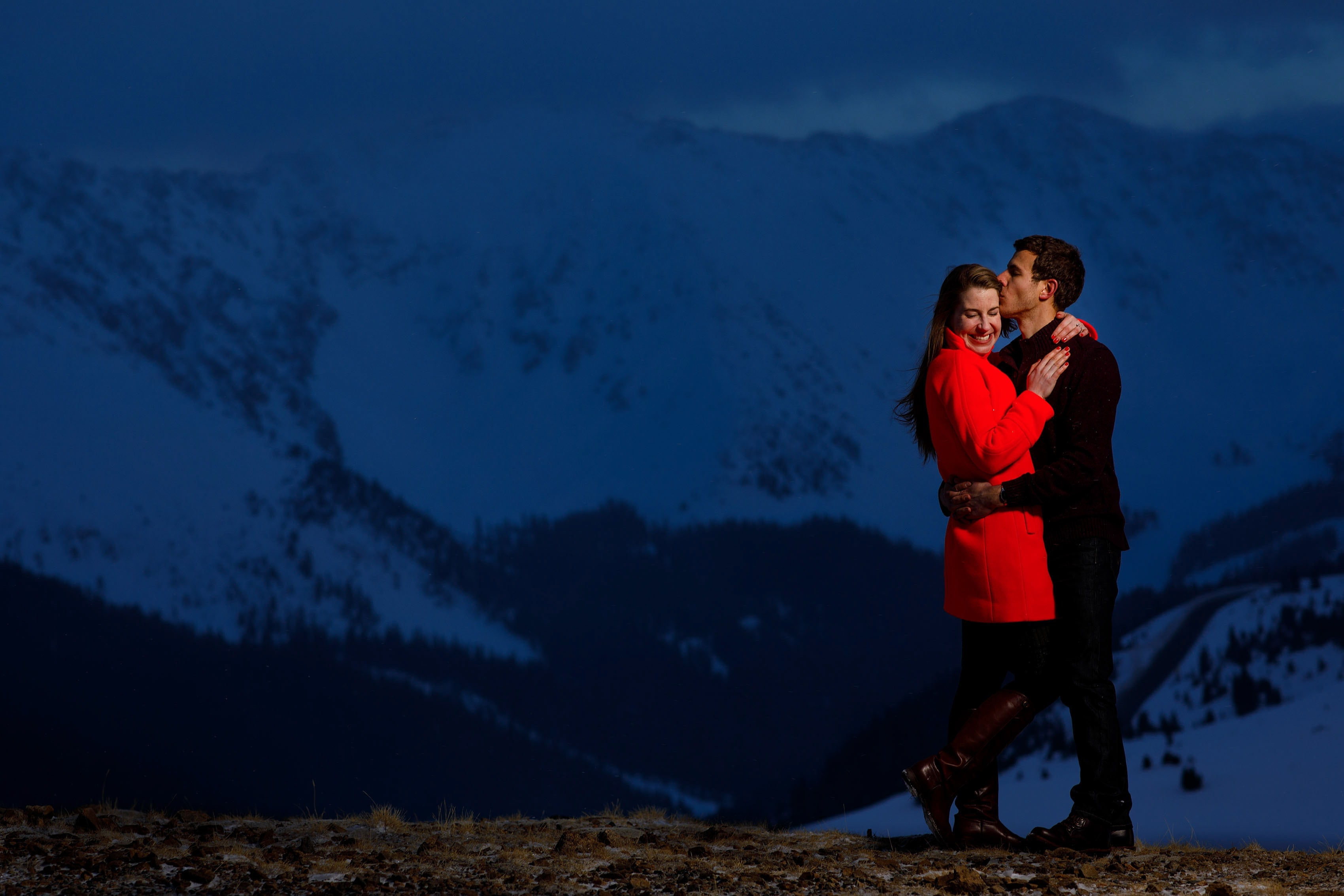 Mike kisses Jessica in a red coat on the top of Loveland Pass at twilight during their Keystone engagement