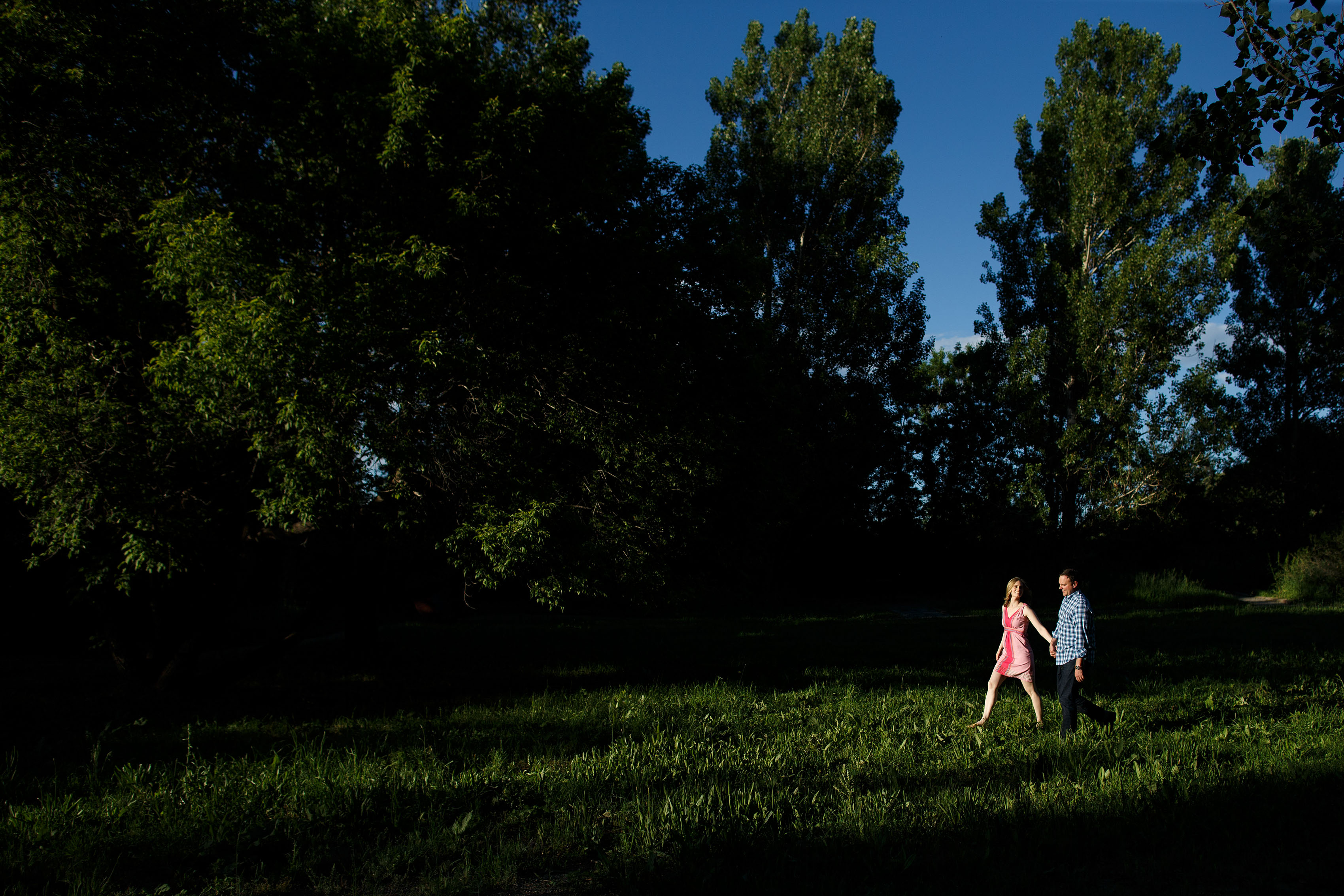Kristy and Jonathan walk together towards sunlight in a grove of trees at Eldorado Springs