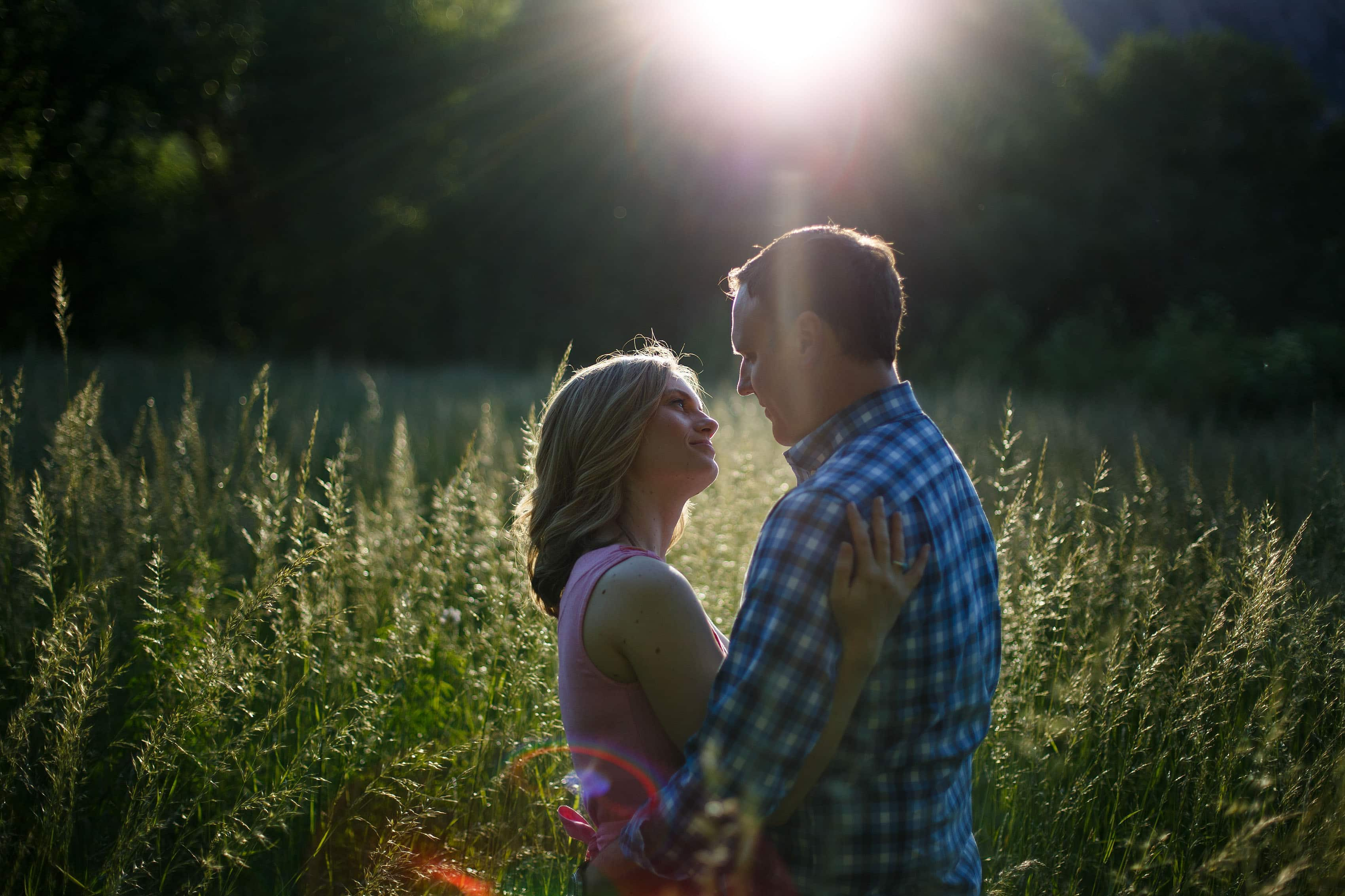 The sun sets over the flatirons as a couple embrace in long grass