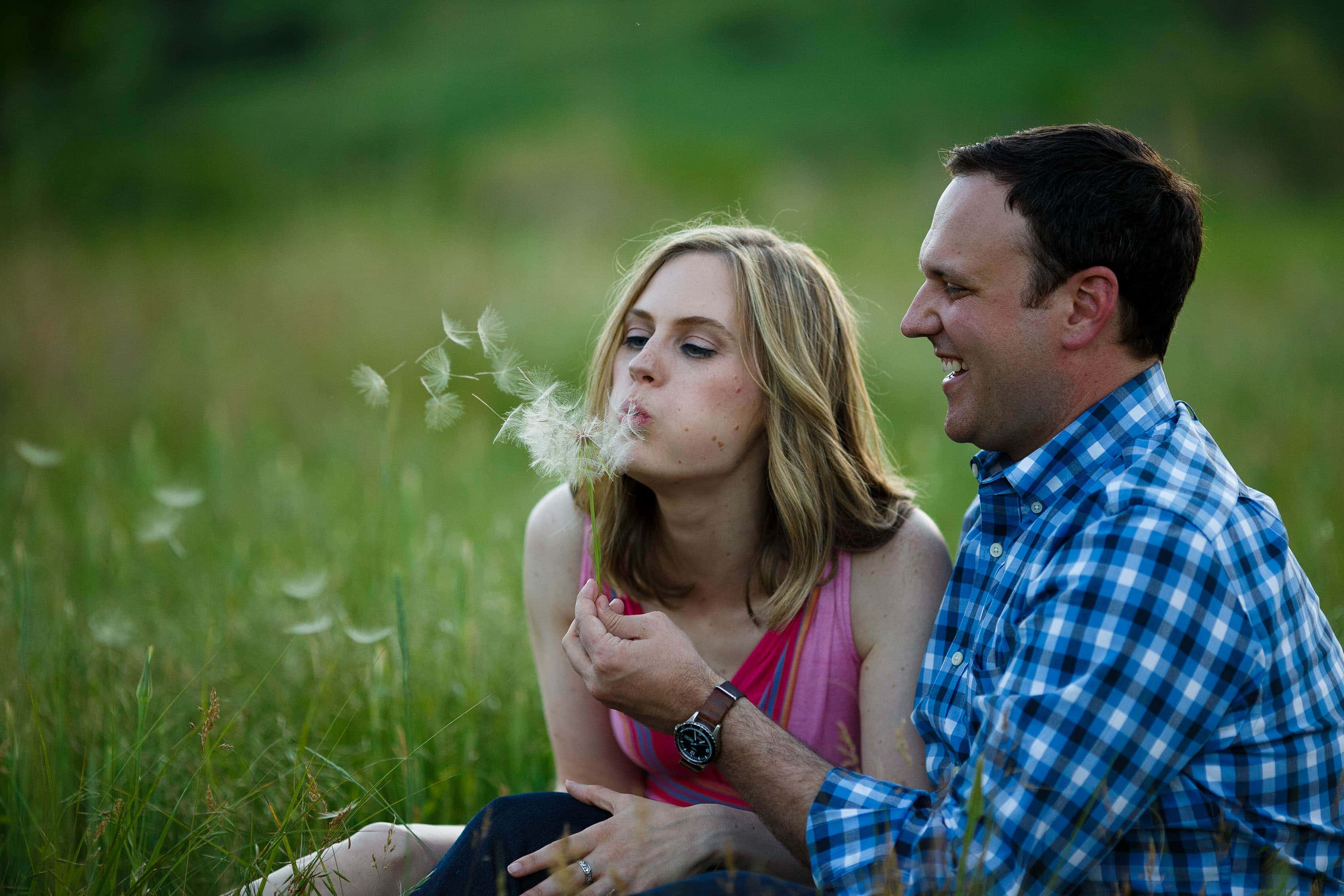 Kristy blows the seeds off of a dandelion during their engagement session