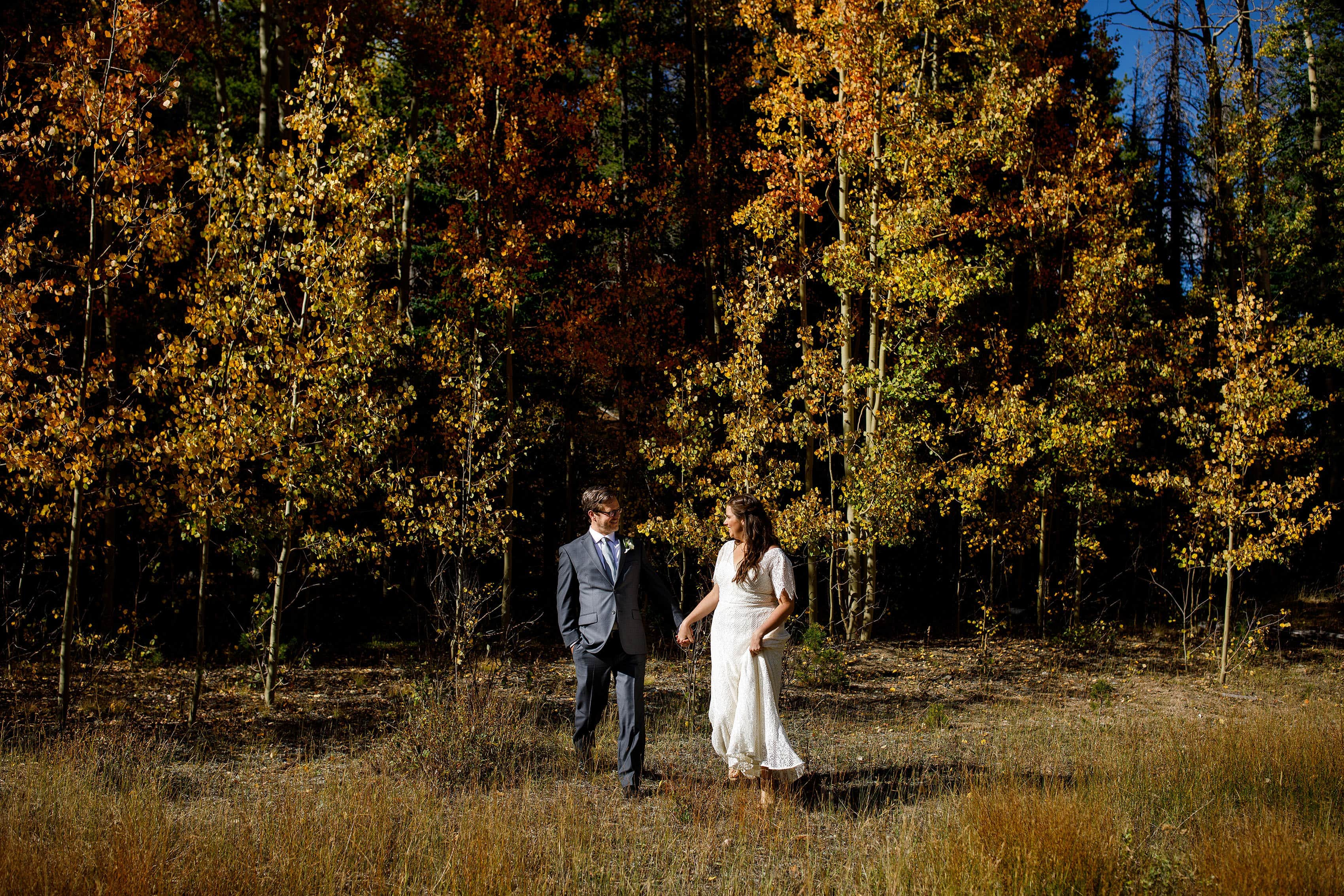 Newlyweds walk together in the fall colors near Blackstone Rivers Ranch
