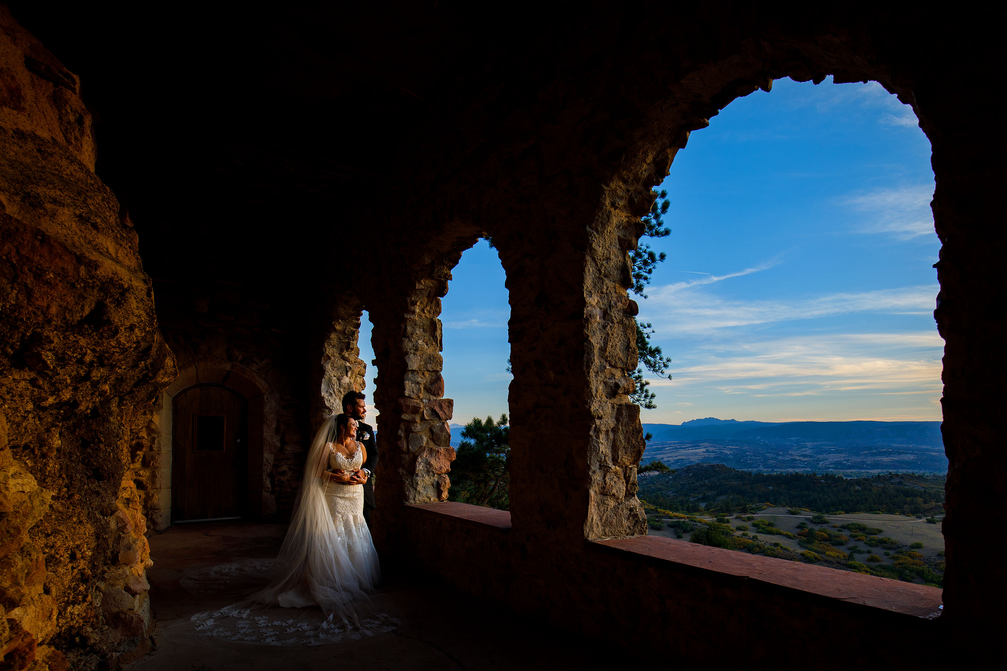 A bride and groom embrace at sunset in the archways at Cherokee Ranch and Castle Foundation