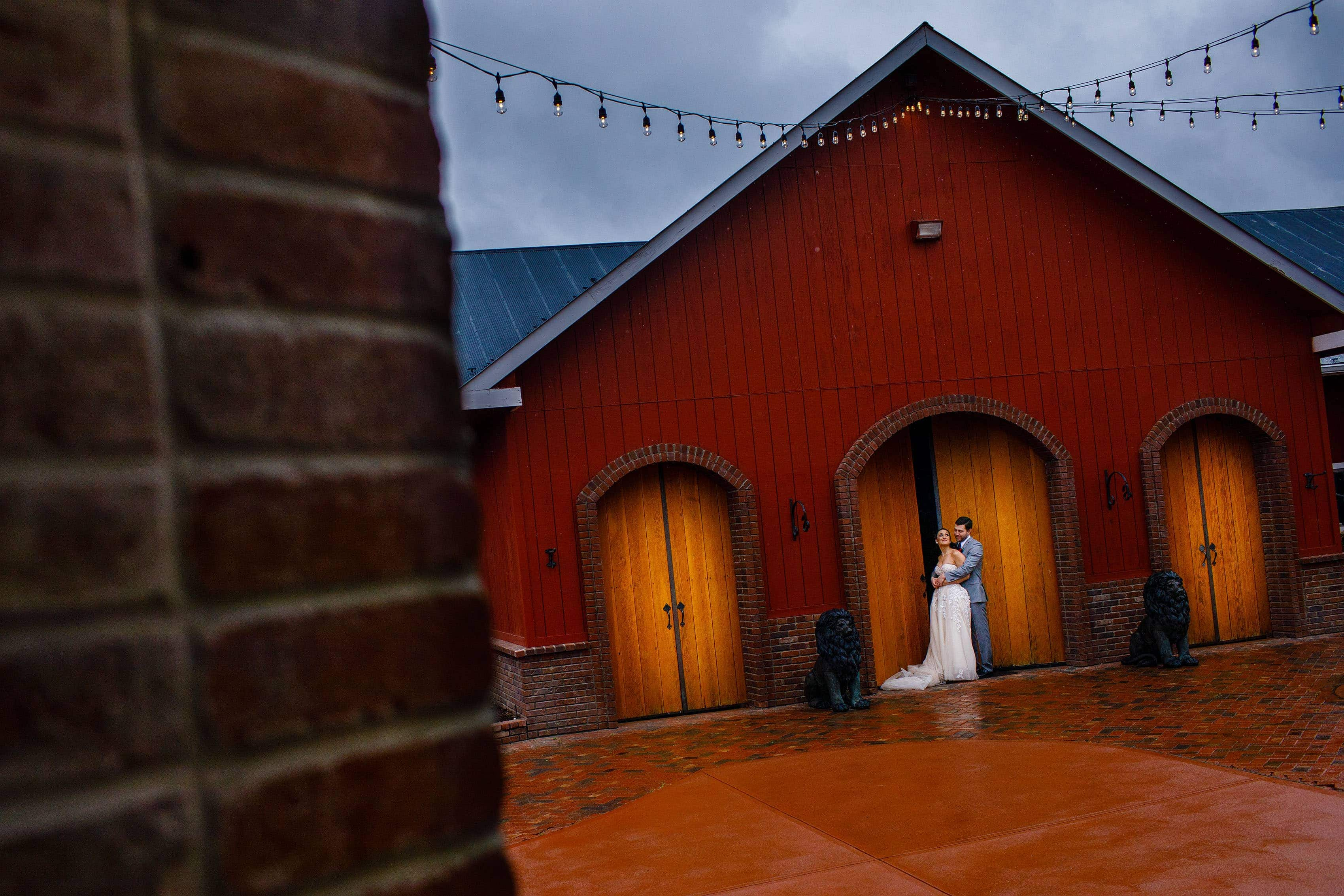 Newlyweds embrace in the courtyard at Crooked Willow Farms during their wedding