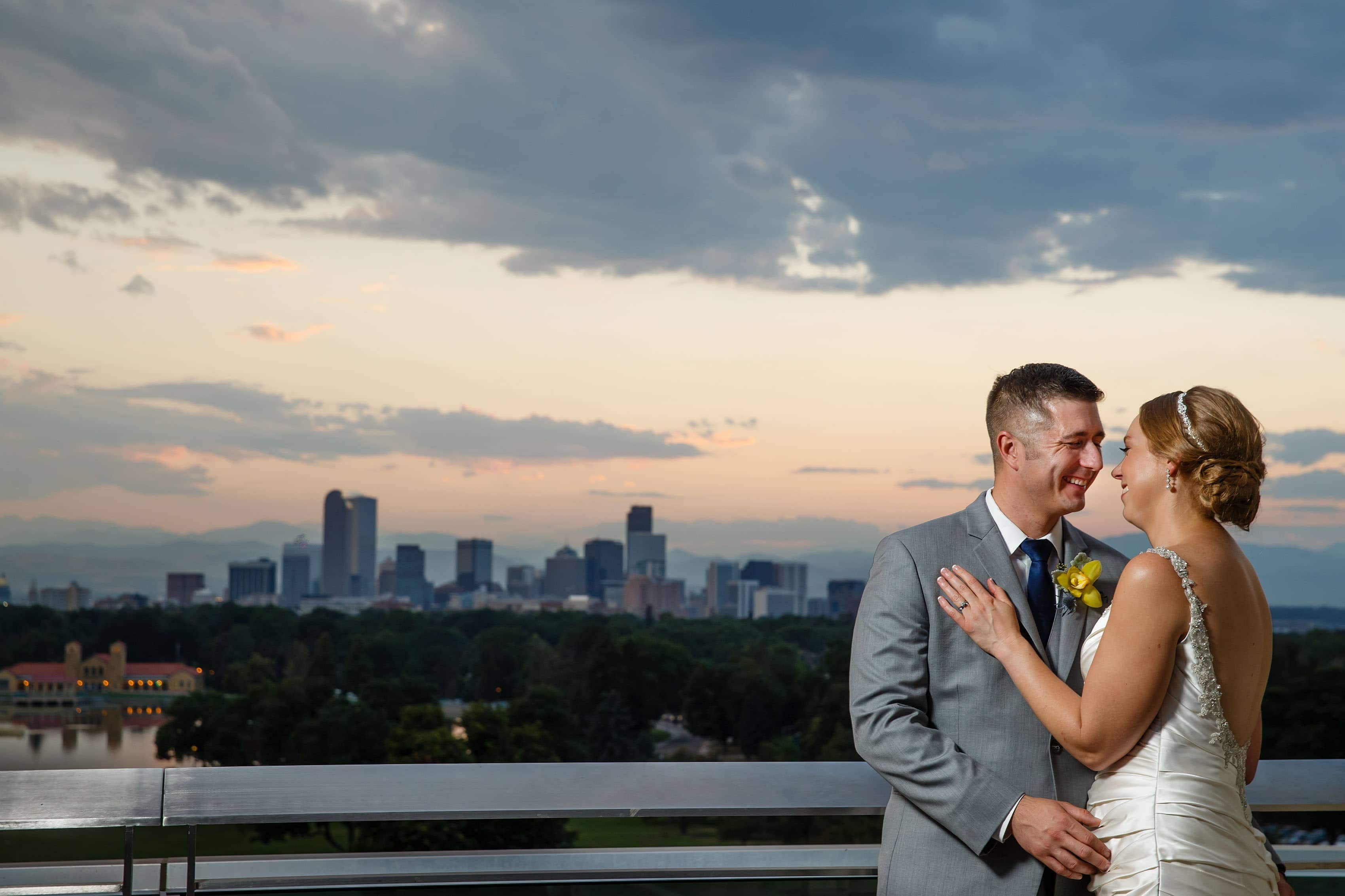 Newlyweds pose in front of the Denver skyline