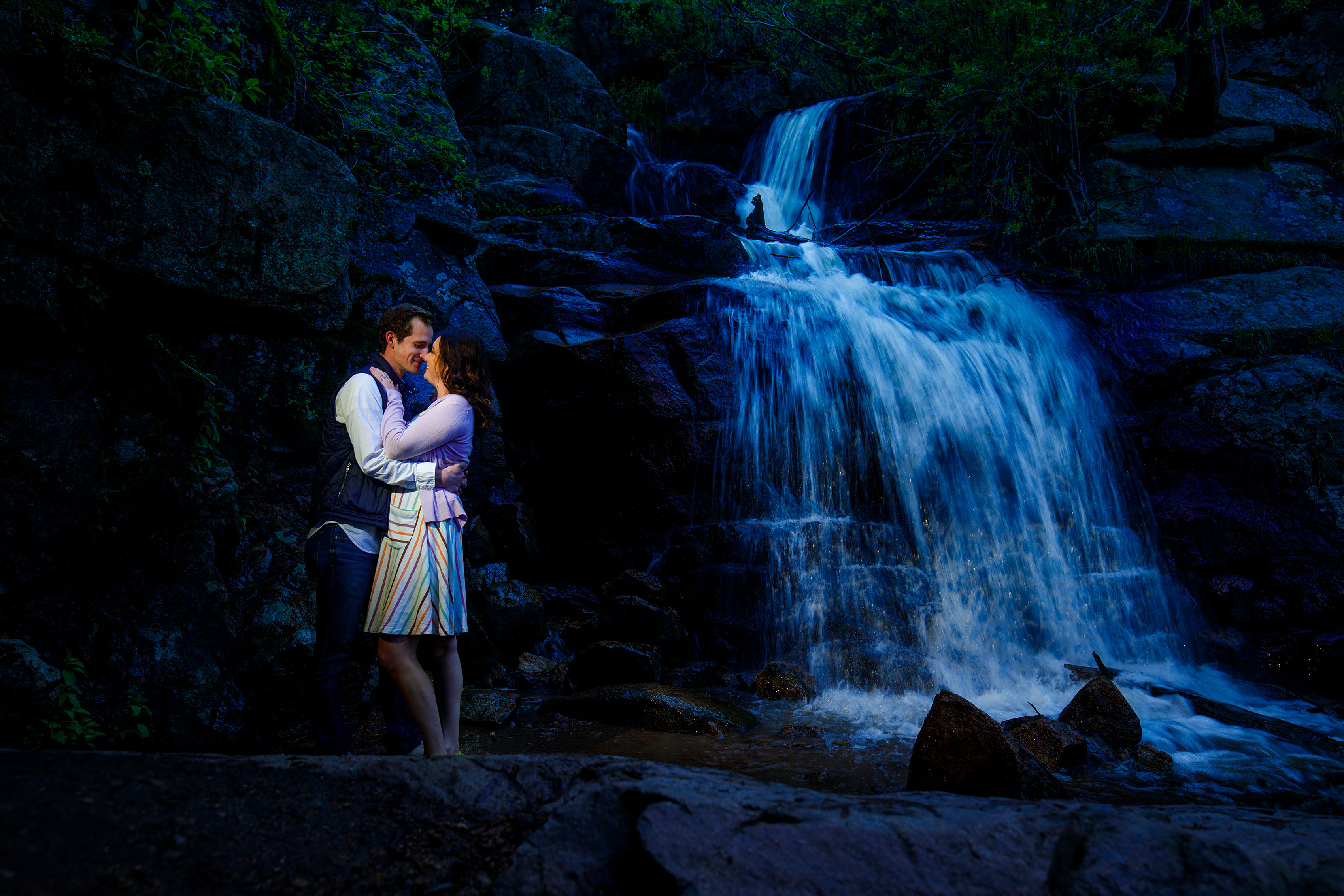 A couple embrace at Maxwell Falls in Evergreen during their engagement photo session