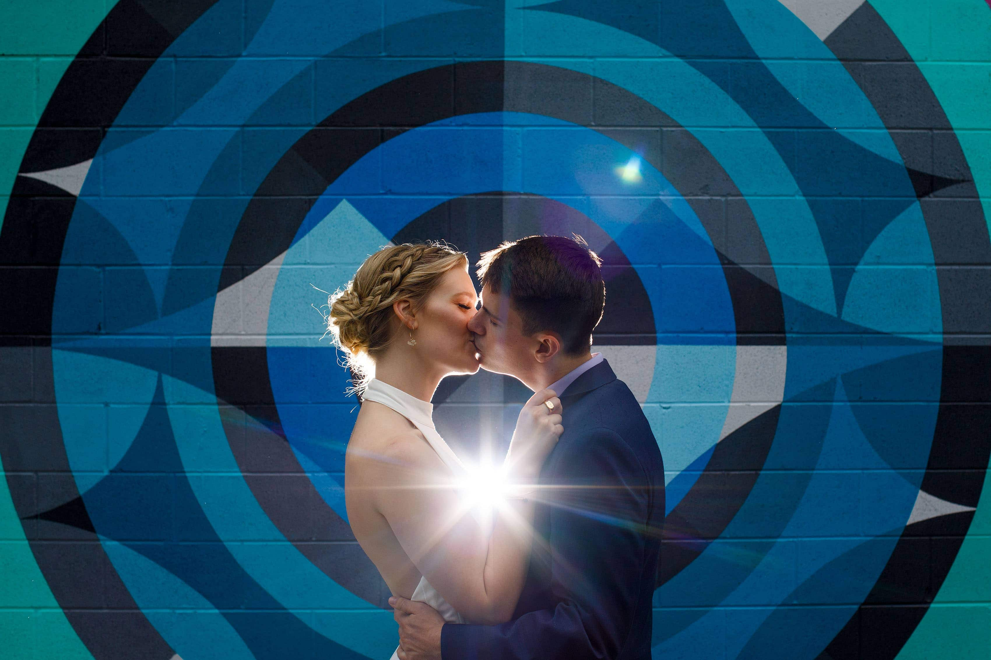 Holly and Hayden share a kiss in front of a mural in the RiNo neighborhood in Denver on their wedding day