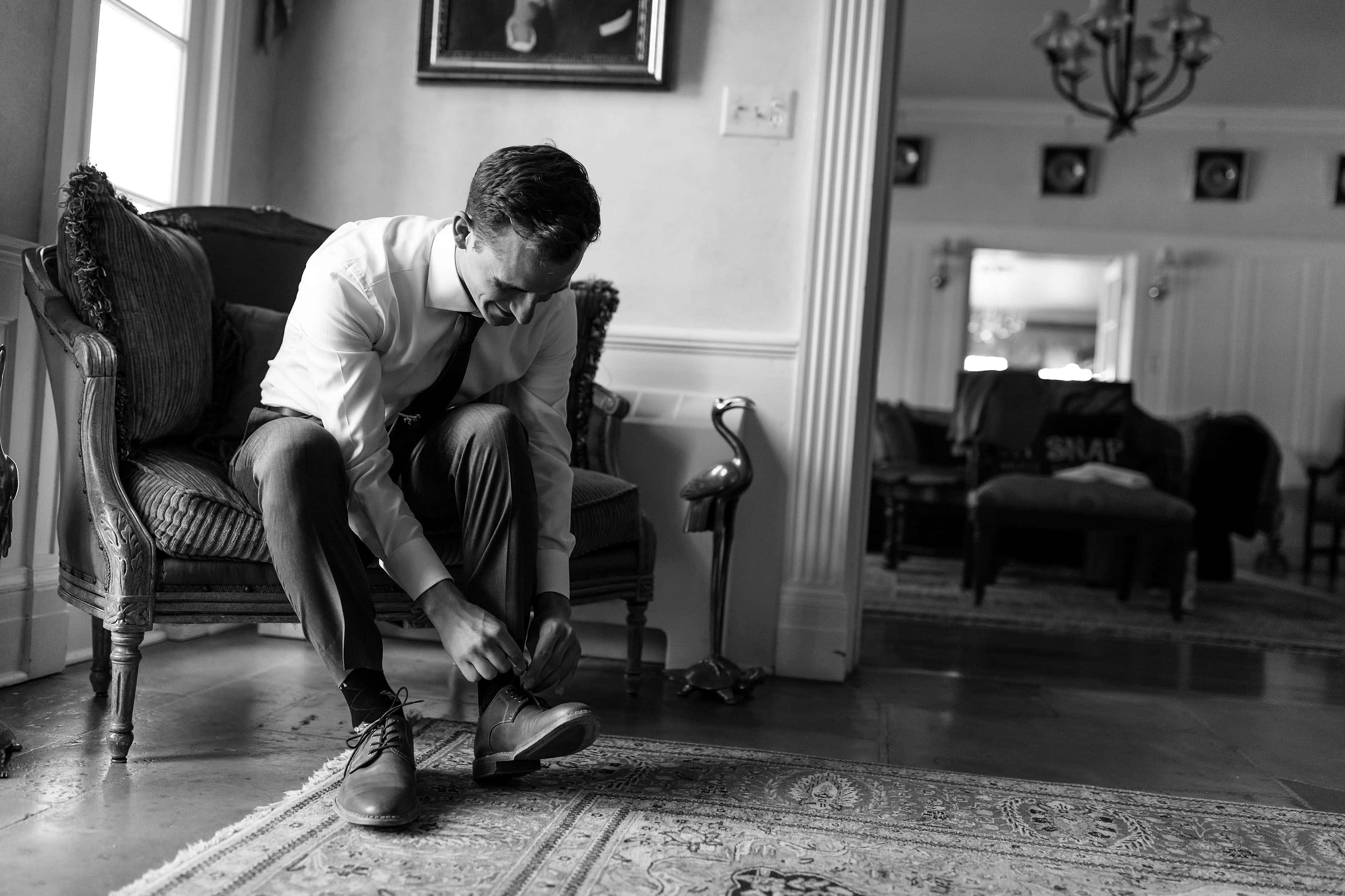 Groom ties his shoes at the Buell Mansion