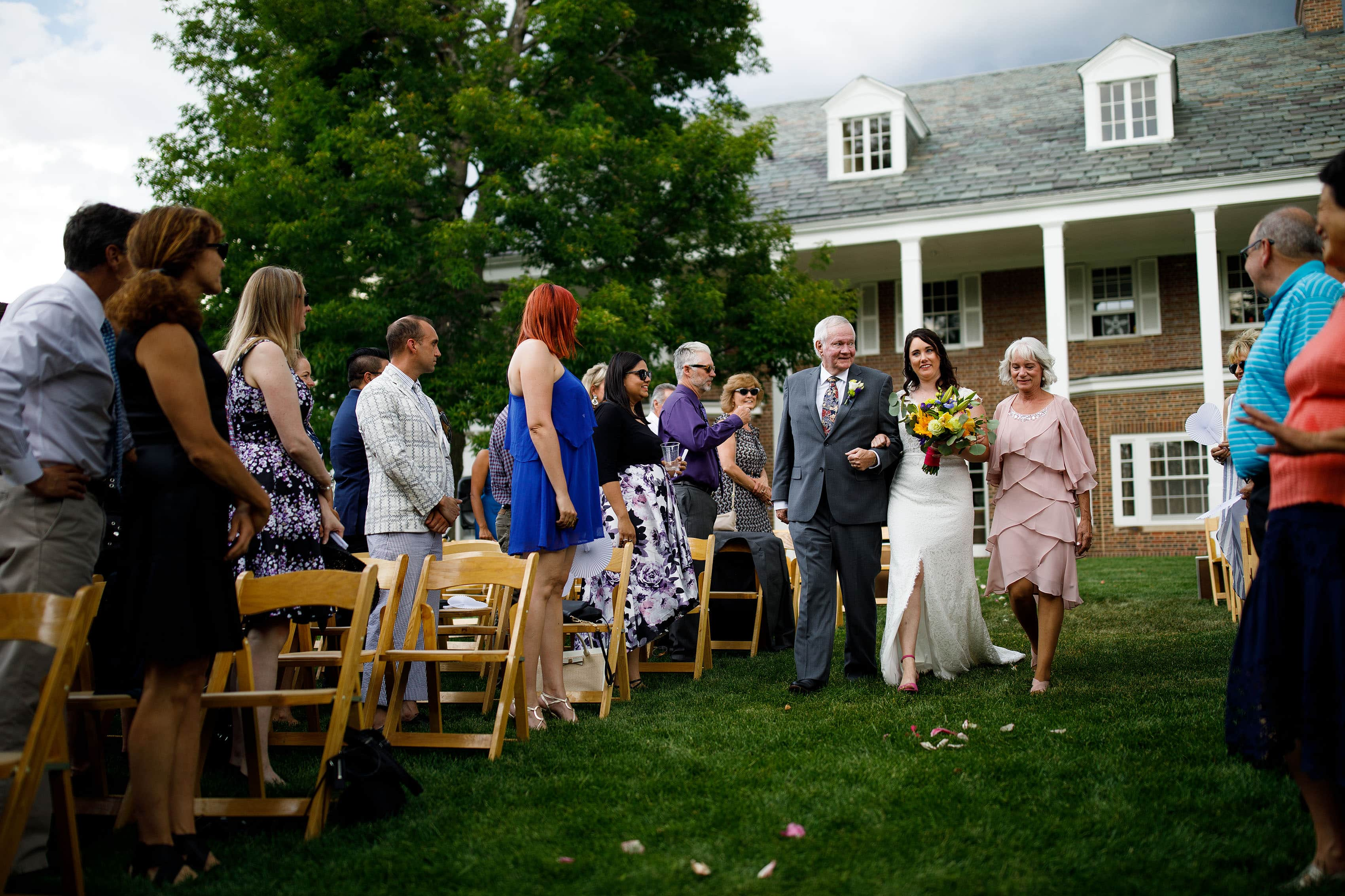 Bride walks down the aisle with her parents at the Buell Mansion
