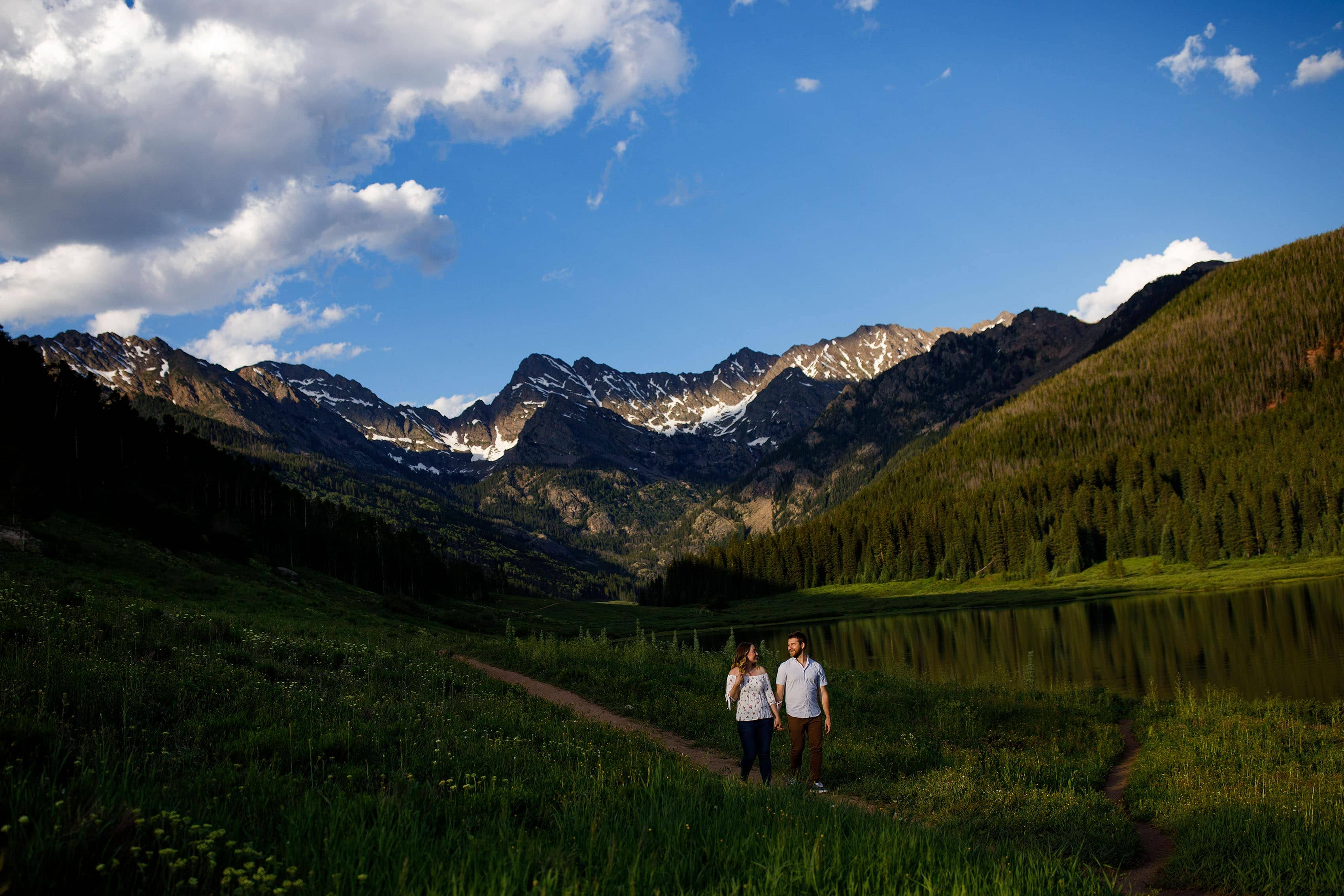 A couple walks together on the trail at Piney Lake with the Gore Range in the background near Vail, CO