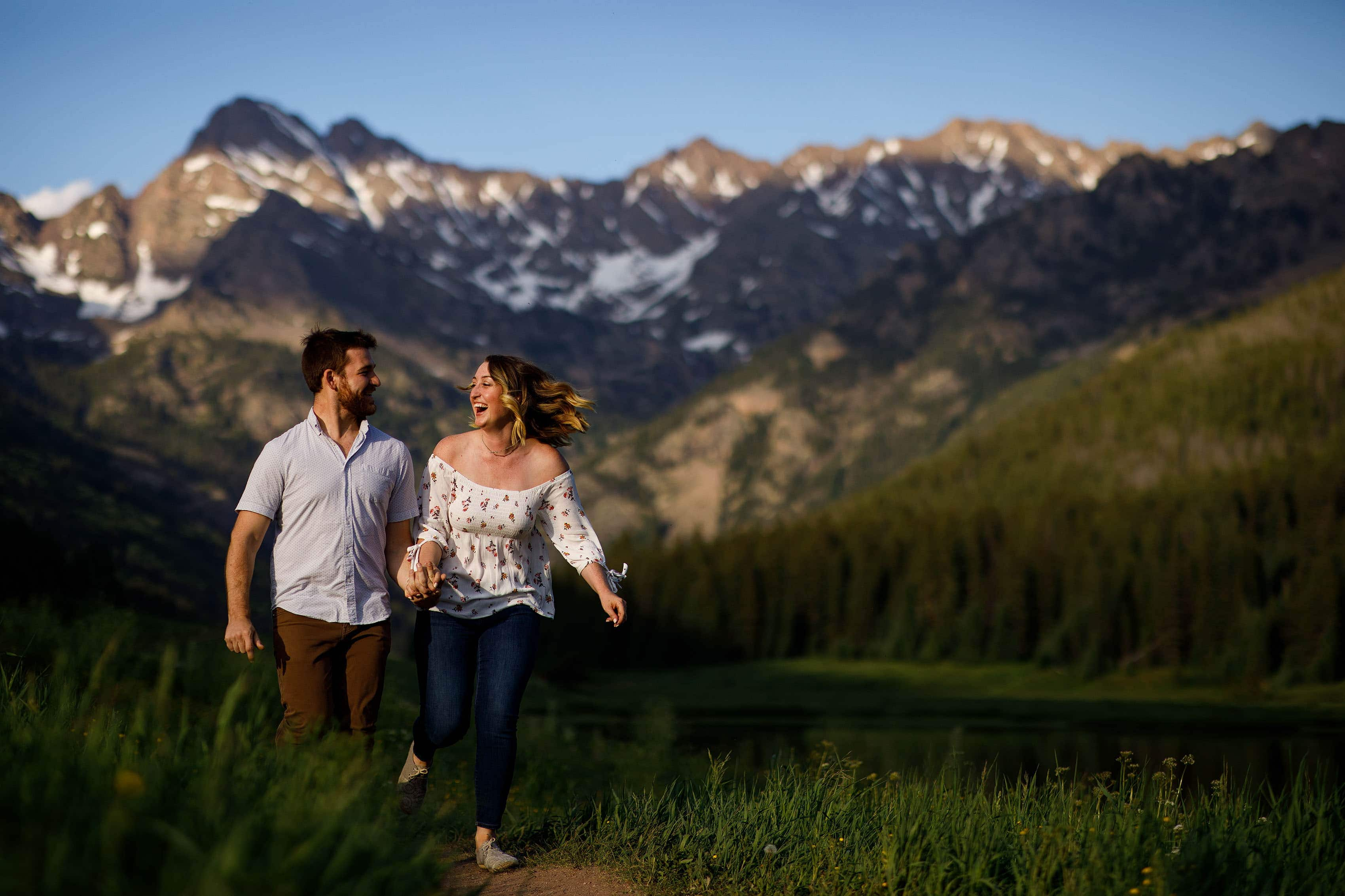 Laura and Ryan laugh and run at Piney River Ranch during their engagement session near Vail, Colorado