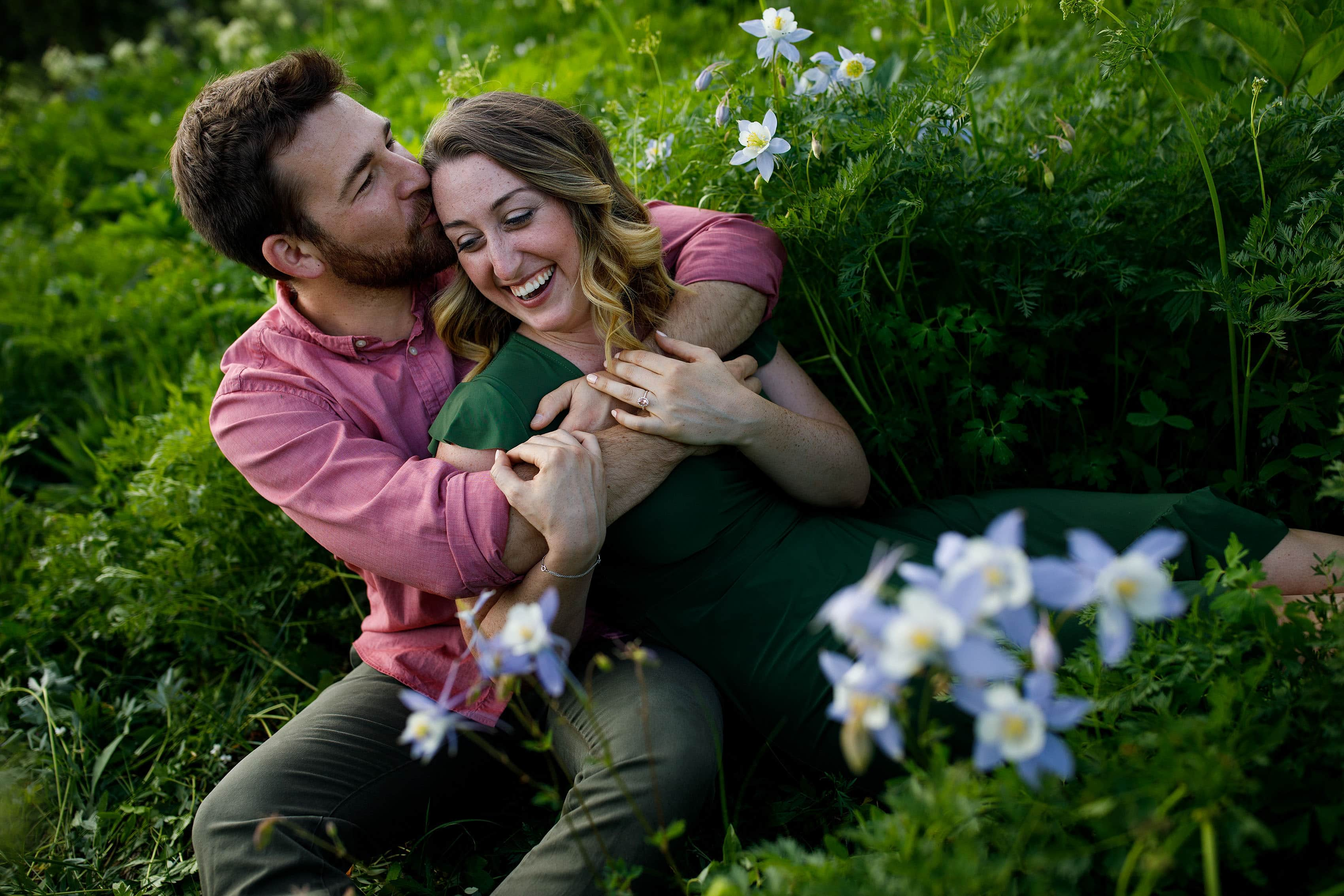 Laura and Ryan share a moment together near Columbine flowers in bloom during their engagement session in Vail, Colorado