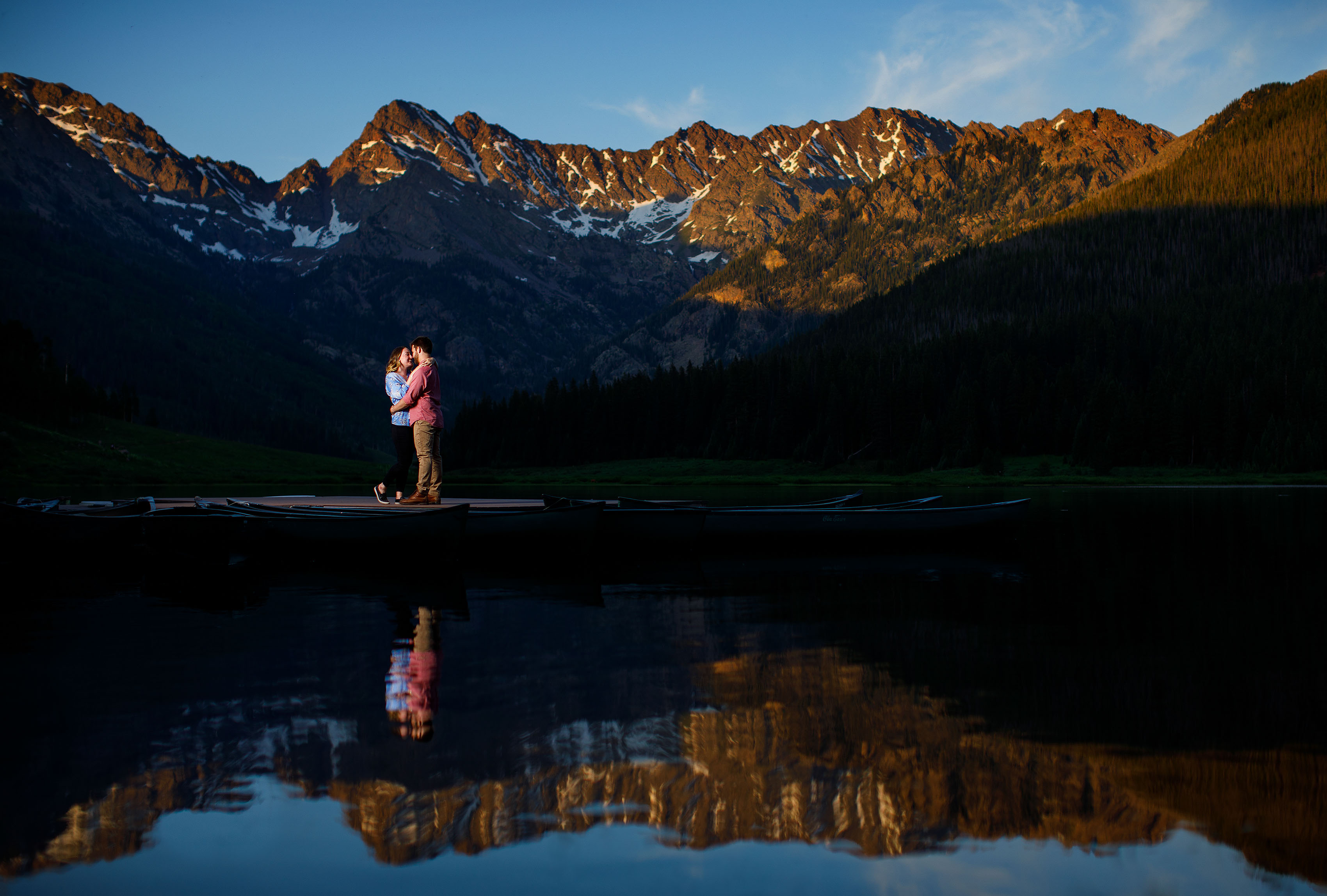 A couple embrace during their Piney River Ranch engagement photos as the Gore Range is reflected in Piney Lake at sunset near Vail, Colorado