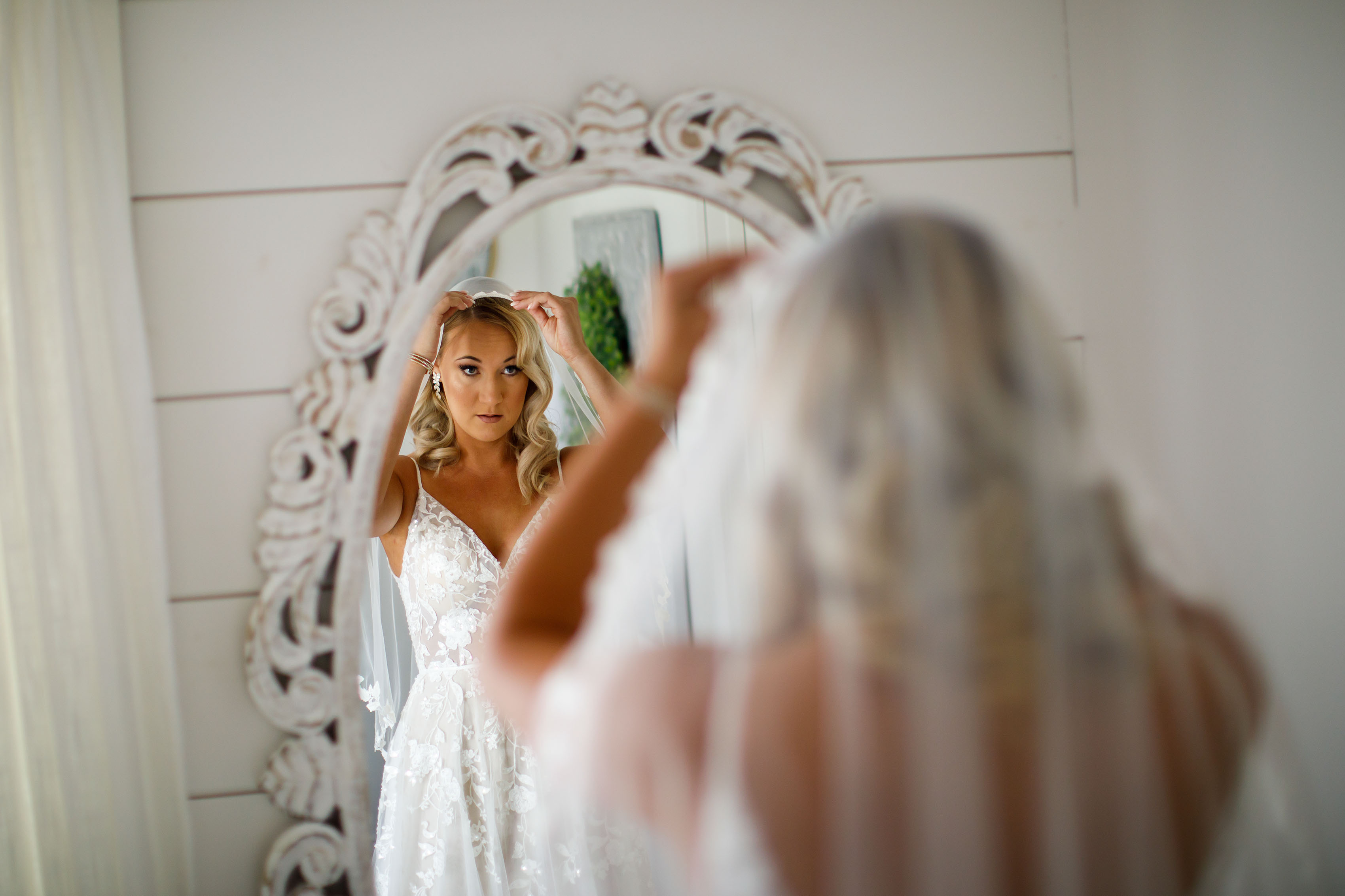 Bride looks in a fintage mirror and adjusts her veil