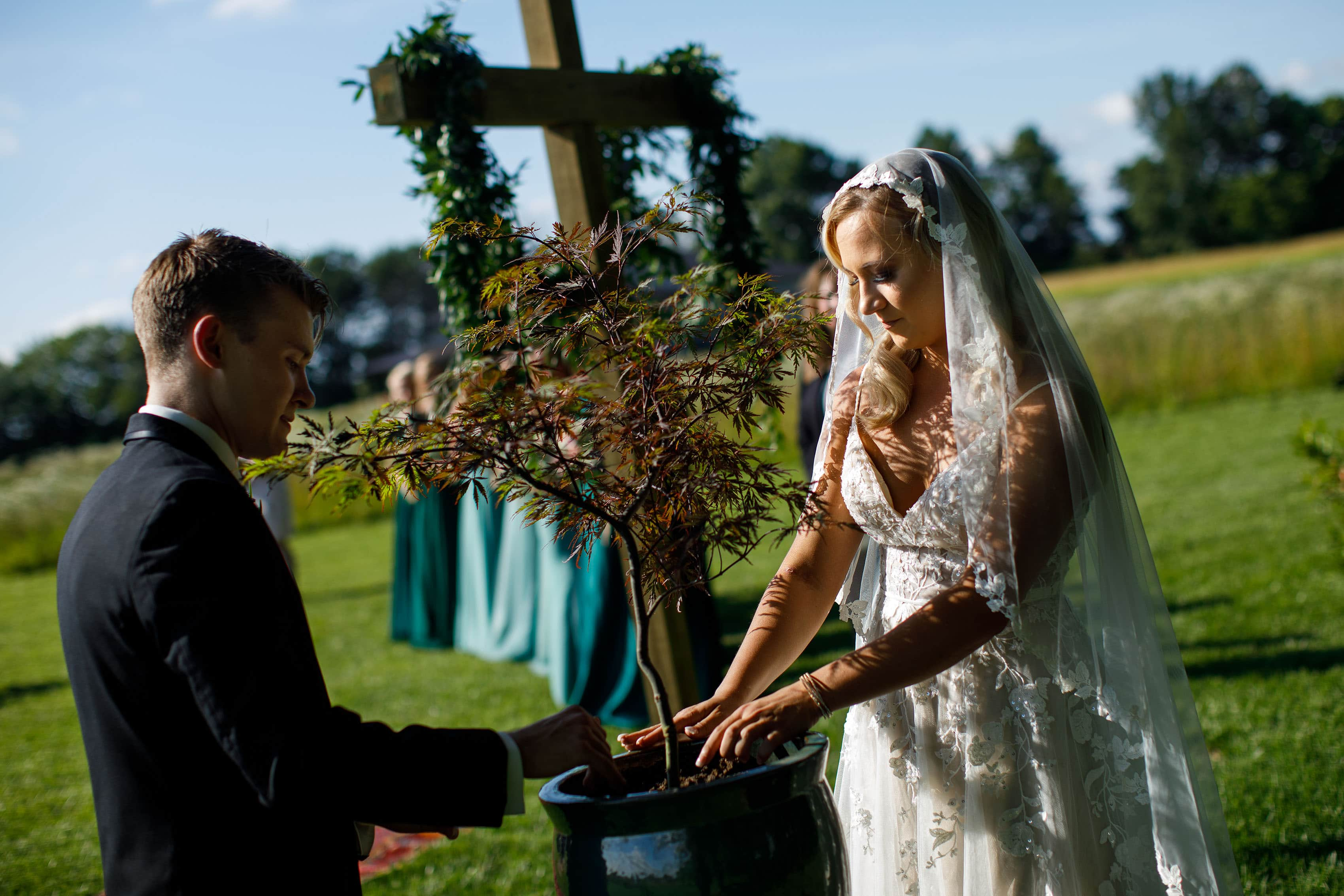 A bride and groom pot a tree during their wedding ceremony at Emerson Fields