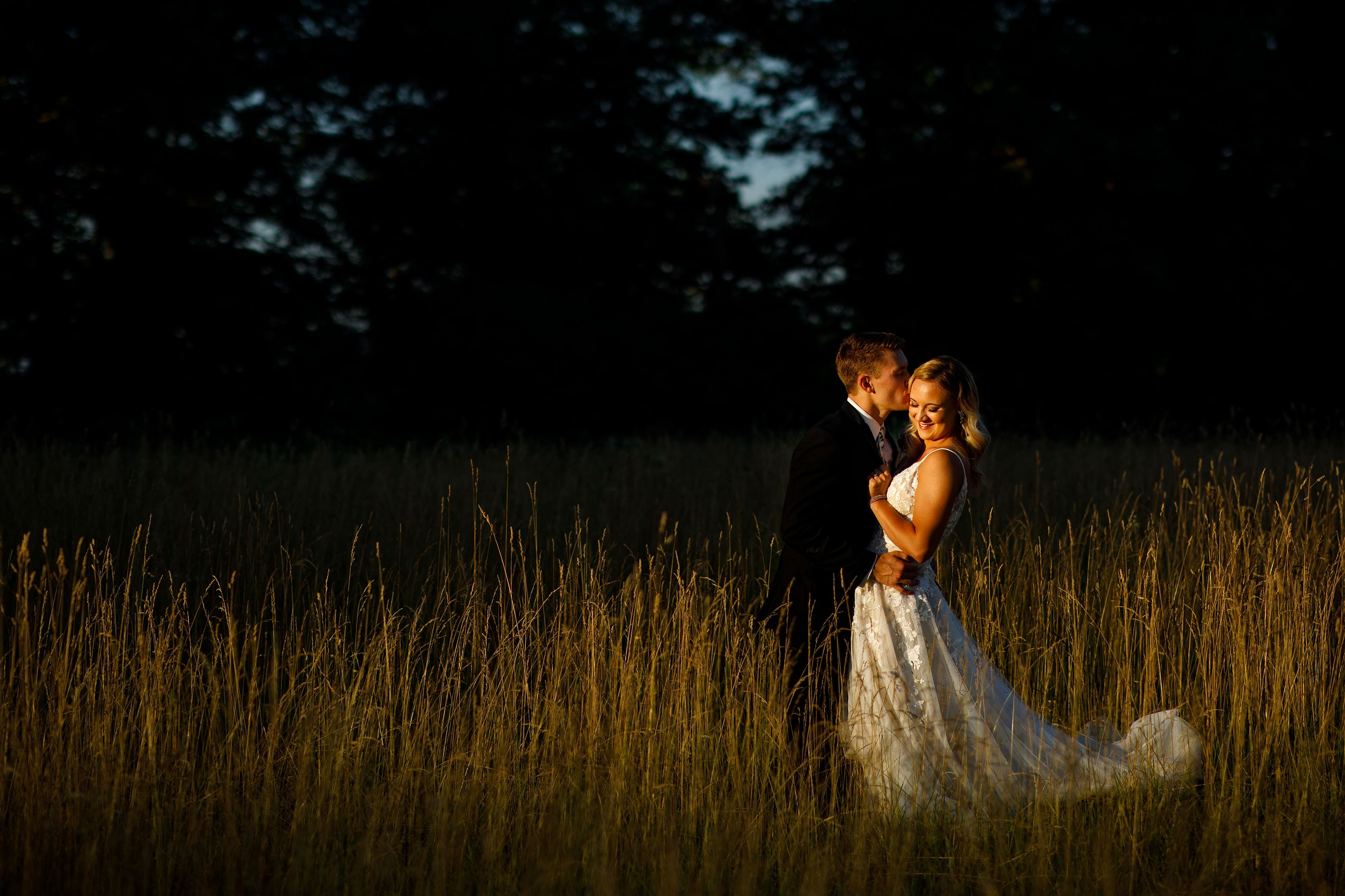 Jacob kisses Sienna in tall grass at Emerson Fields during golden hour on their wedding day