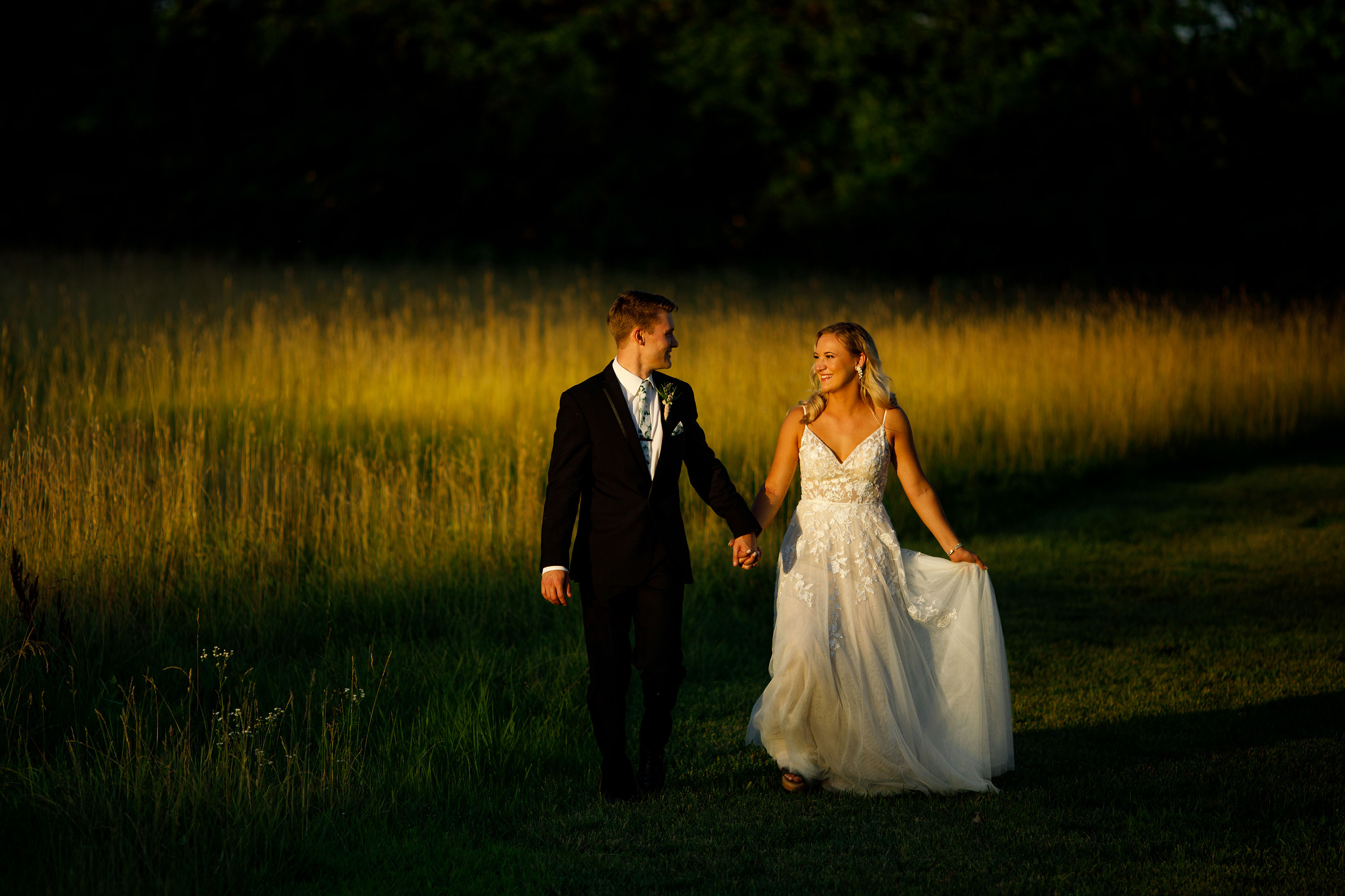 The newlyweds walk together at golden hour during their summer Emerson Fields wedding in Excello, Missouri