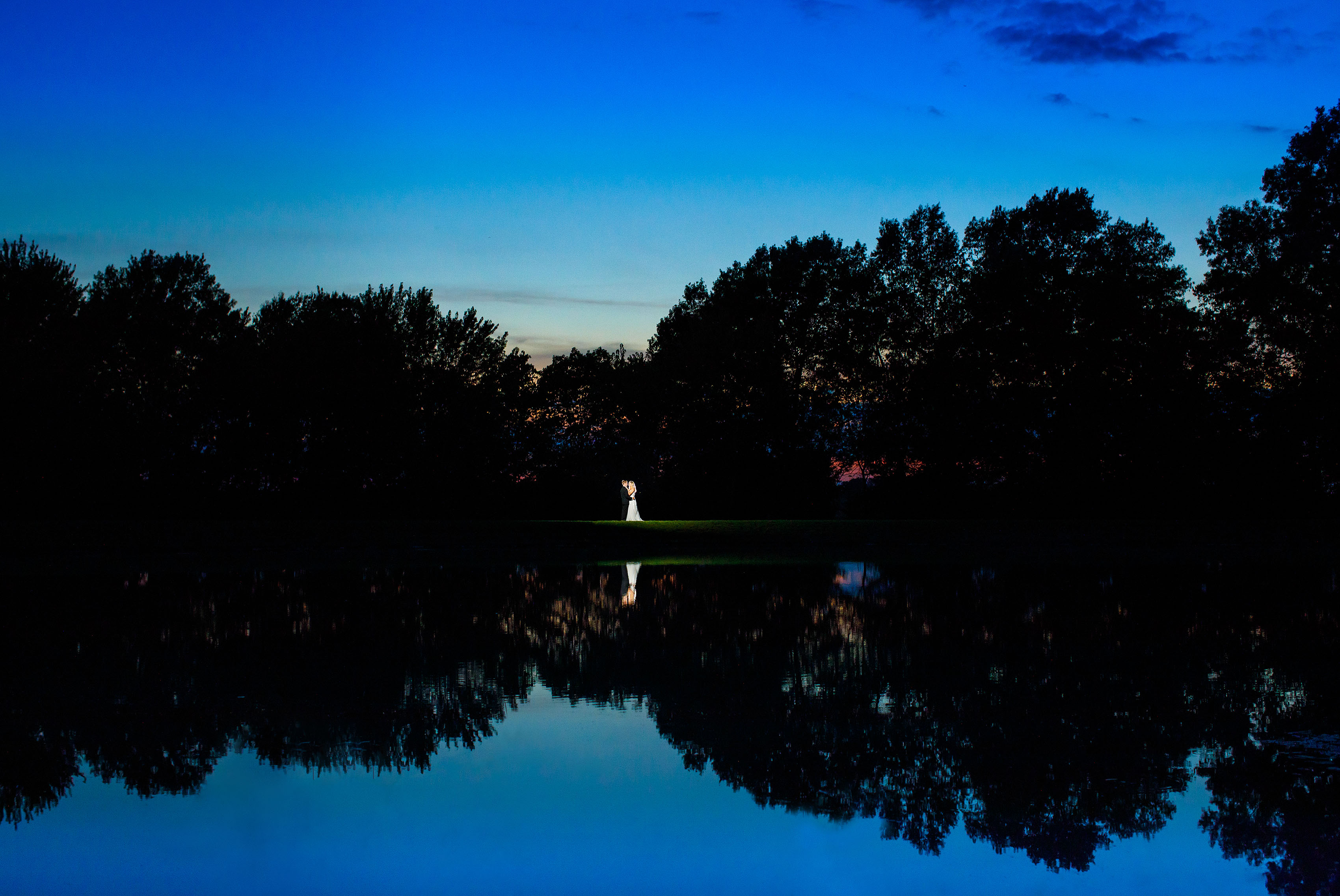 Jacob and Sienna are reflected in the pond while posing for a portrait during their summer Emerson Fields wedding at sunset