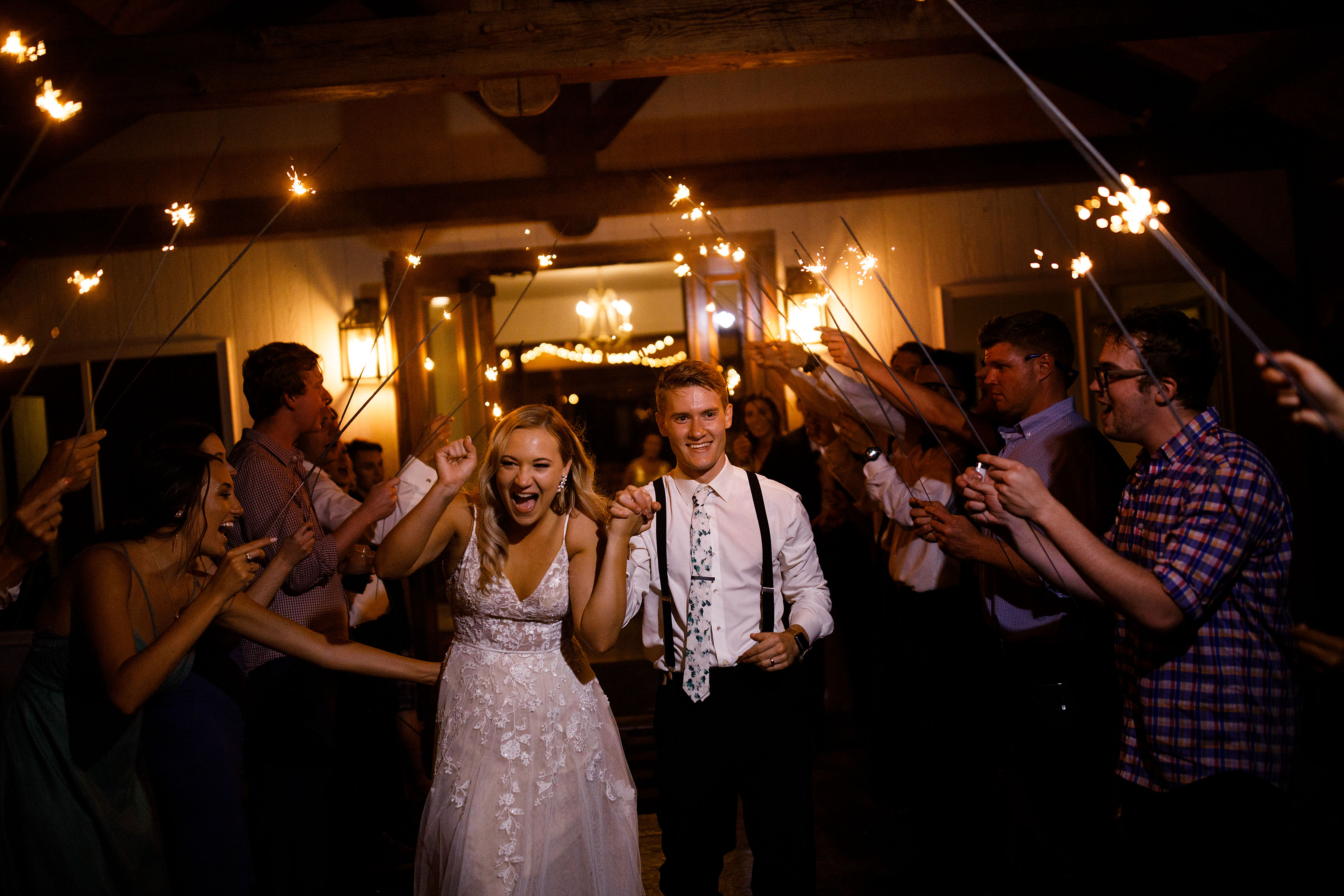 The newlyweds exit their Emerson Fields wedding through a tunnel of sparklers