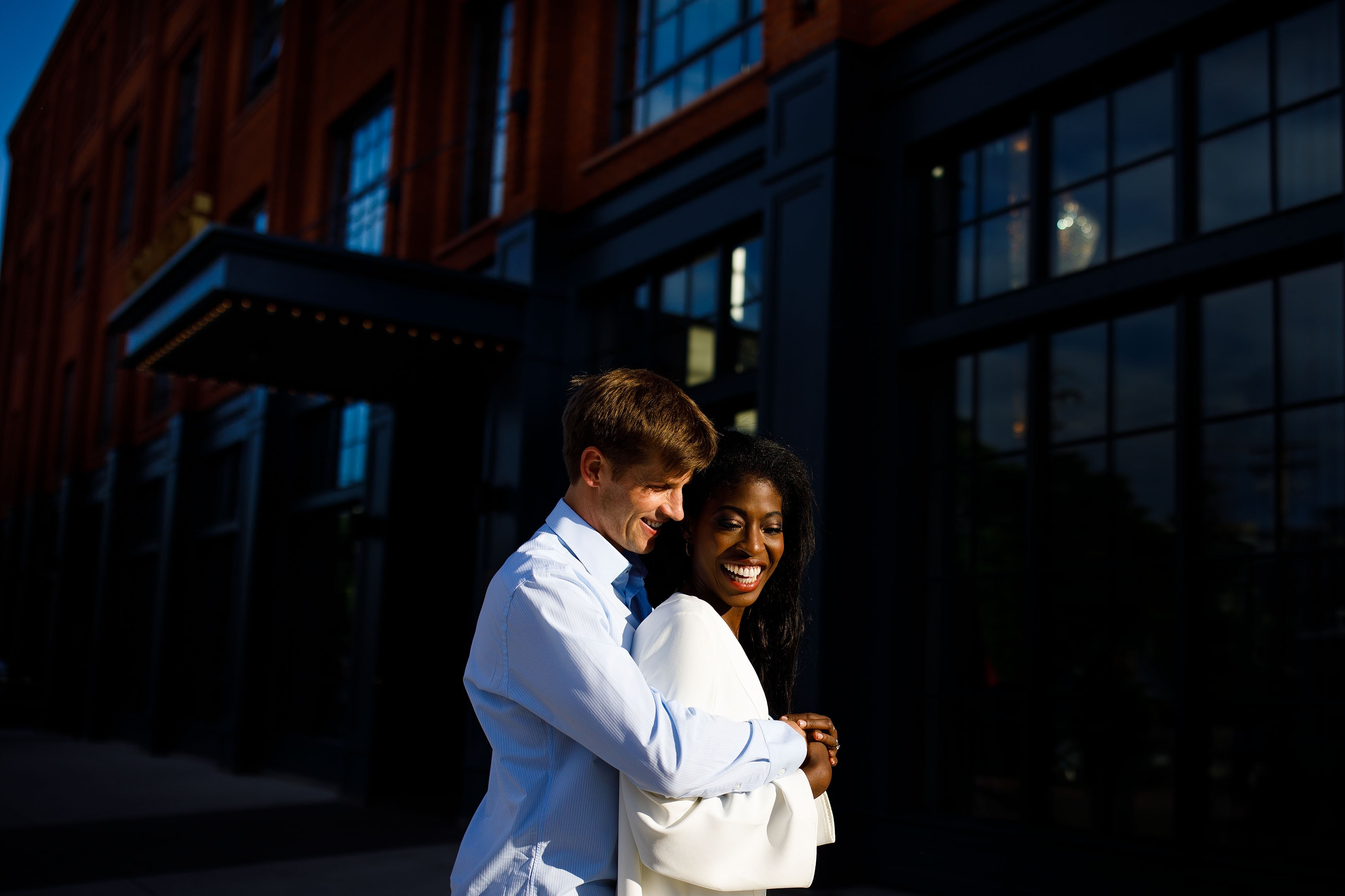 Ewo and Henry embrace outside The Ramble Hotel during their downtown engagement photos