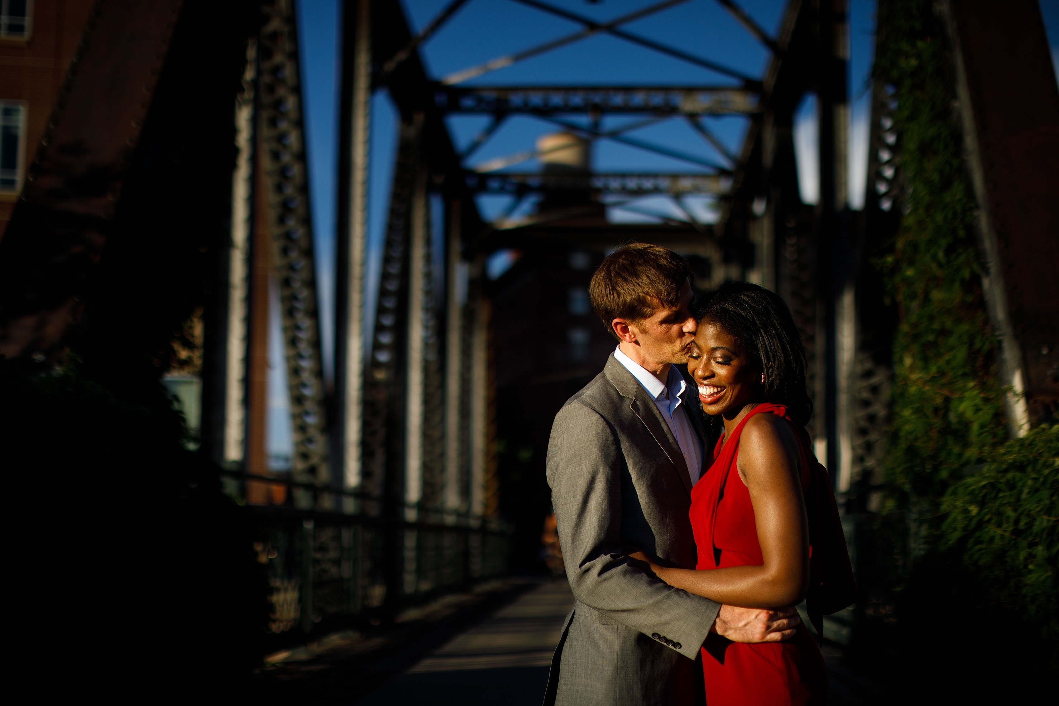 Henry kisses Ewo during golden hour at the Wynkoop Street Bridge in downtown Denver's Lodo neighborhood during their engagement session
