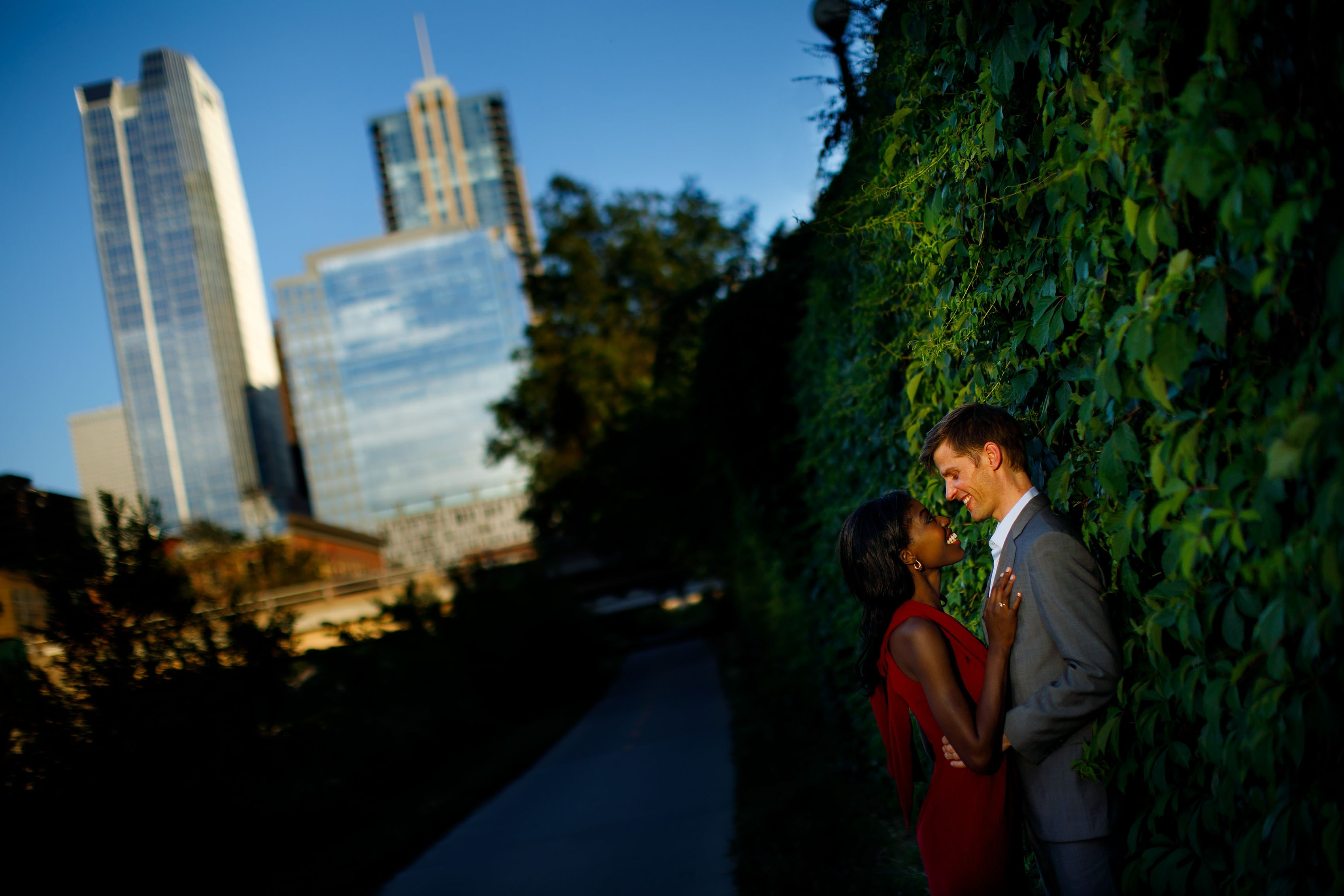 A couple embrace on the Ivy wall along the Cherry Creek path in downtown Denver during their engagement photos