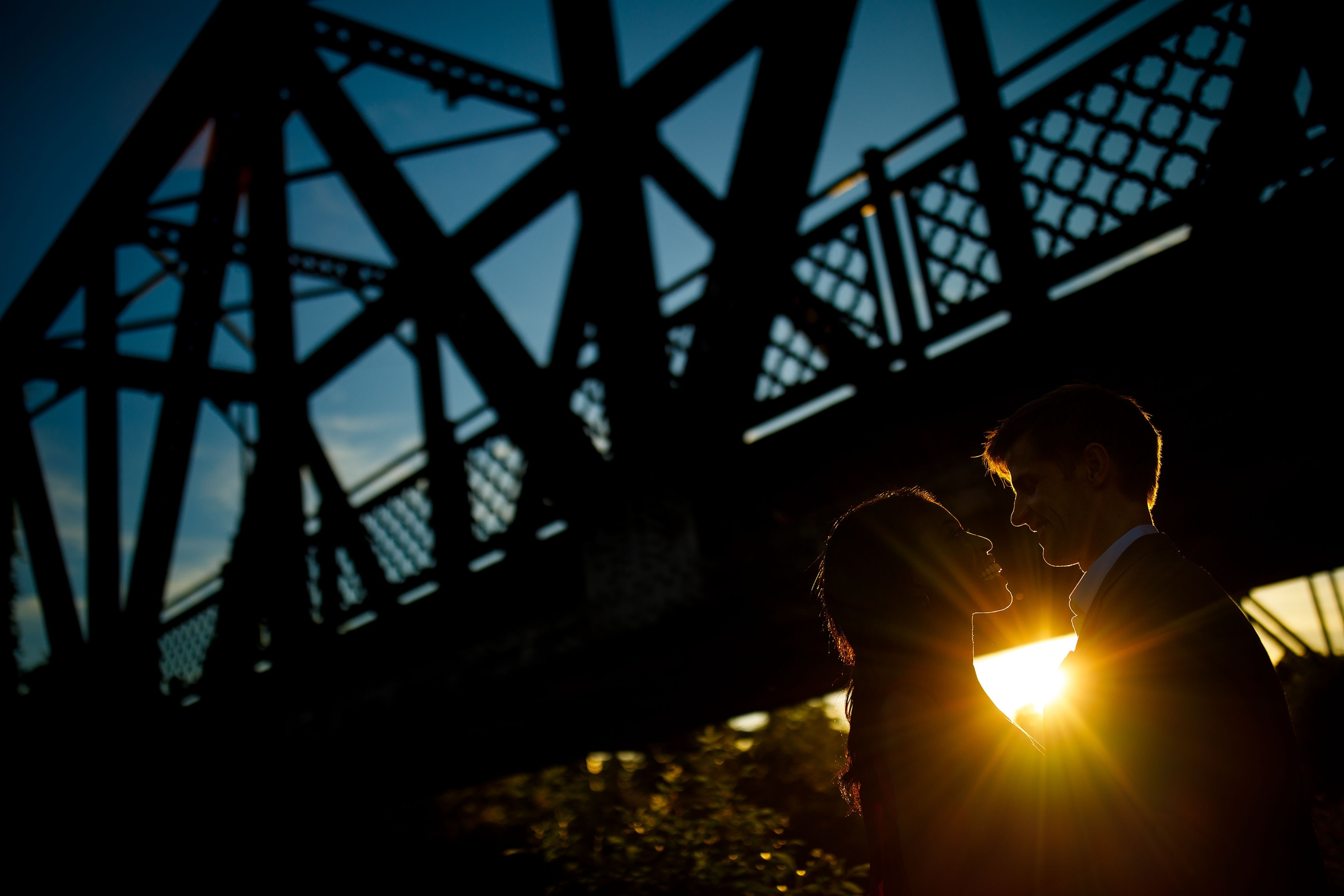 The sun sets behind a couple and the Wynkoop Street Bridge in Denver