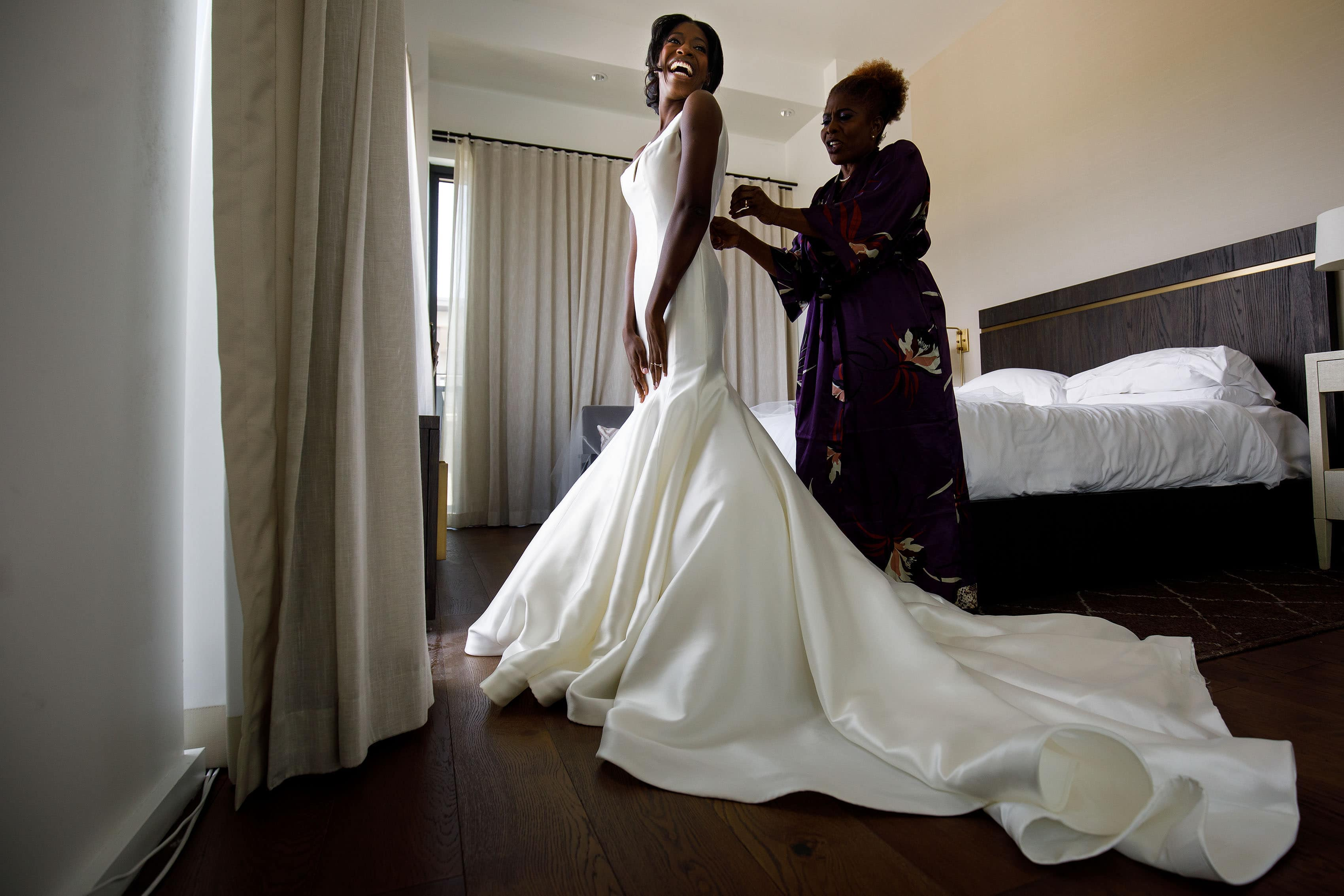 Bride smiles while putting on her wedding dress at the Presidential Suite at the Halcyon Hotel in Cherry Creek North
