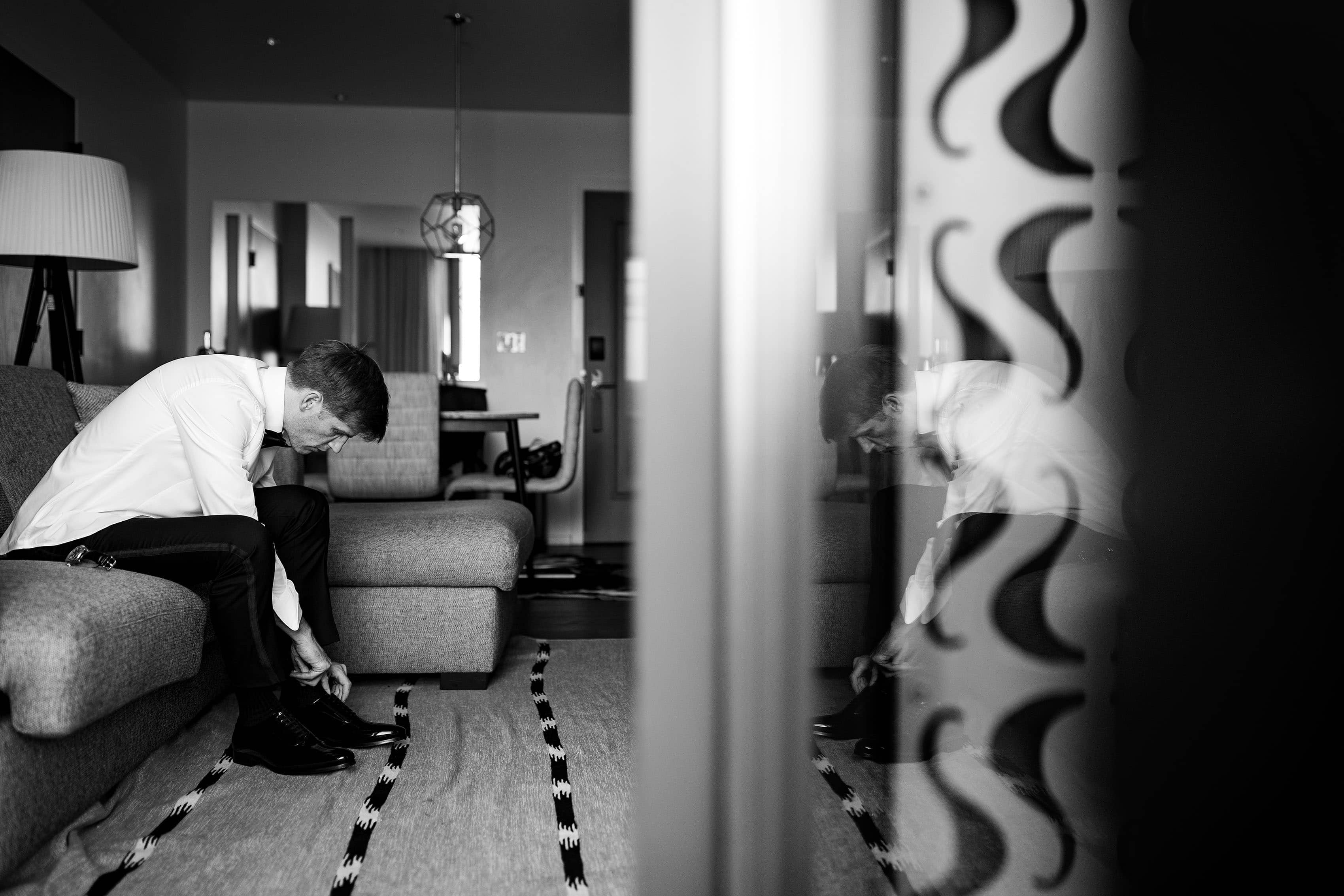 Groom puts on his shoes at the Halcyon hotel in denver on his wedding day