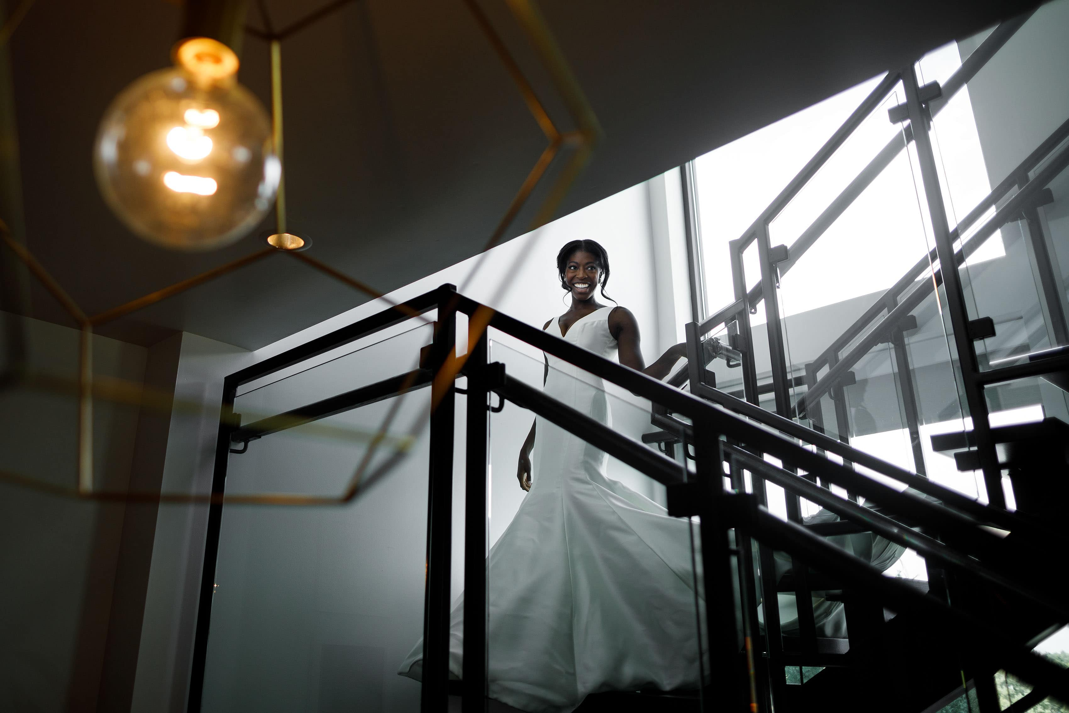 Ewo walks down the stairs at the Halcyon Cherry Creek North presidential suite in her wedding dress