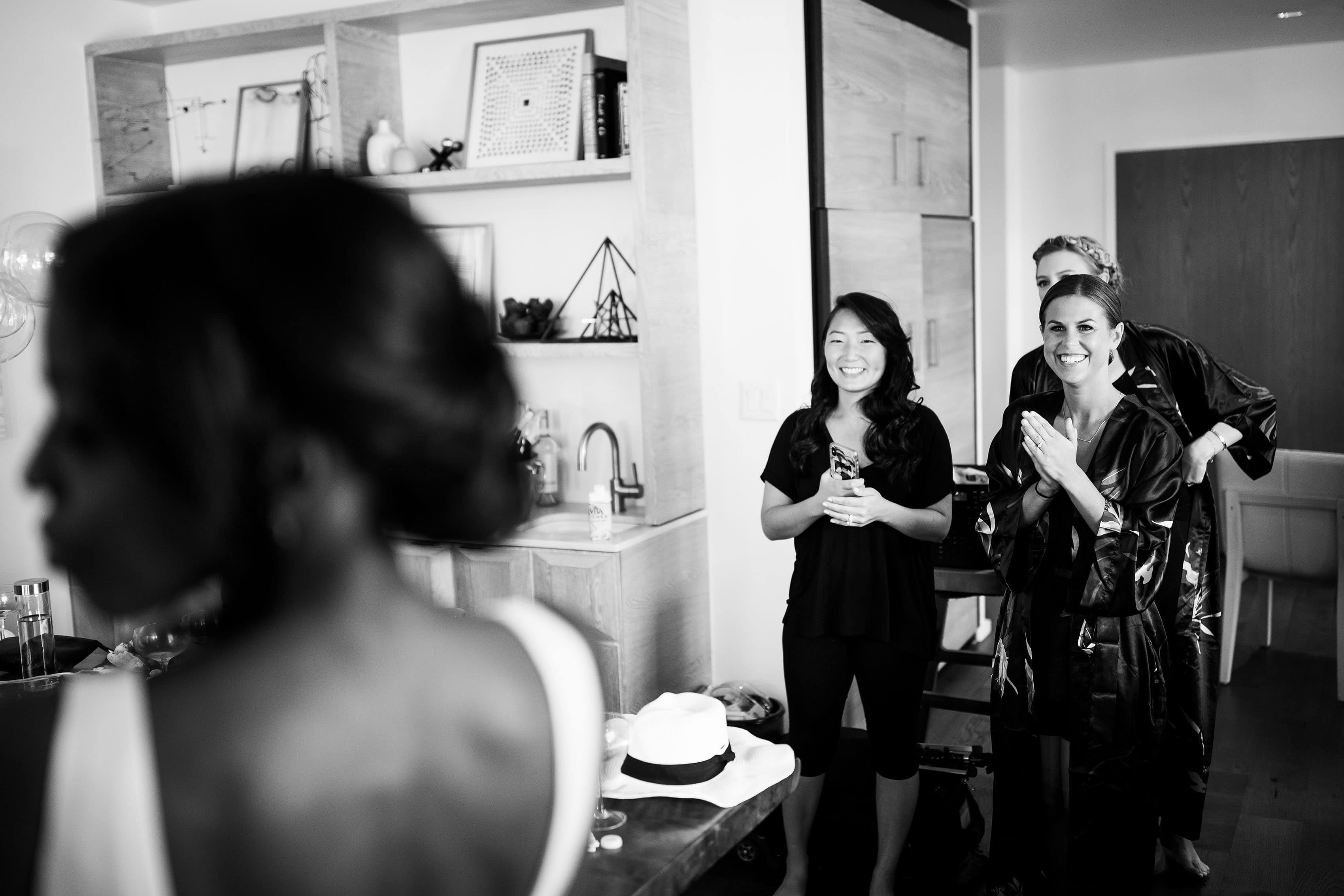 Bridesmaids react in the Halcyon Presidential Suite as the bride gets ready for the wedding