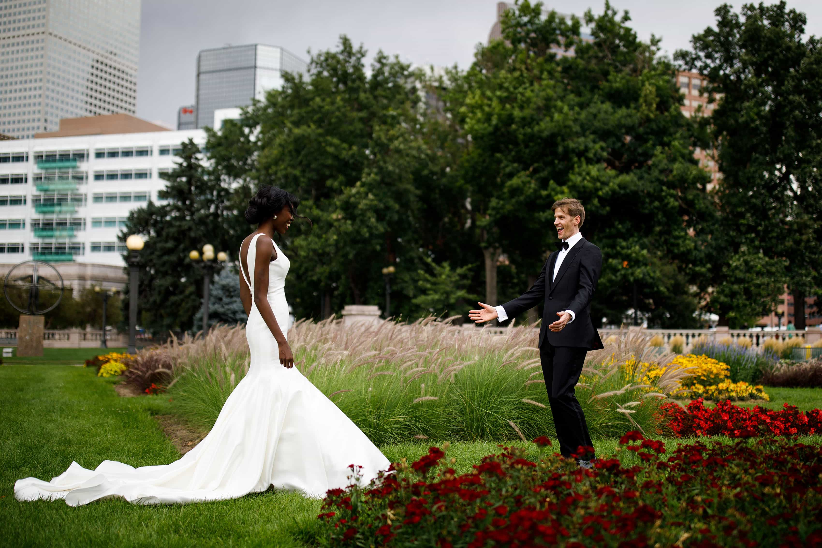 A couple react during their first look in Civic Center Park on their wedding day