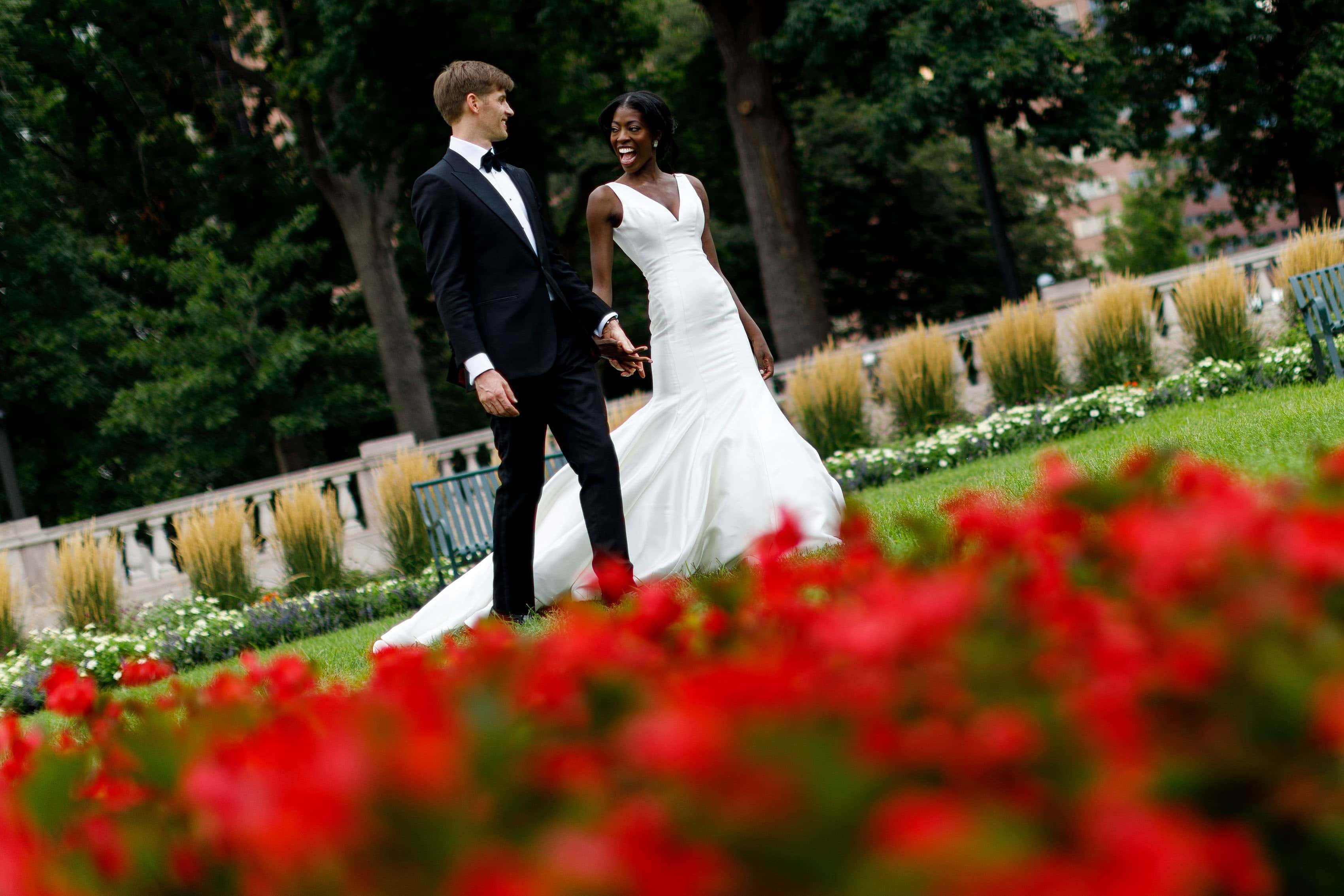 Ewo and Henry walk past colorful flowers in Denver's Civic Center Park on their wedding day