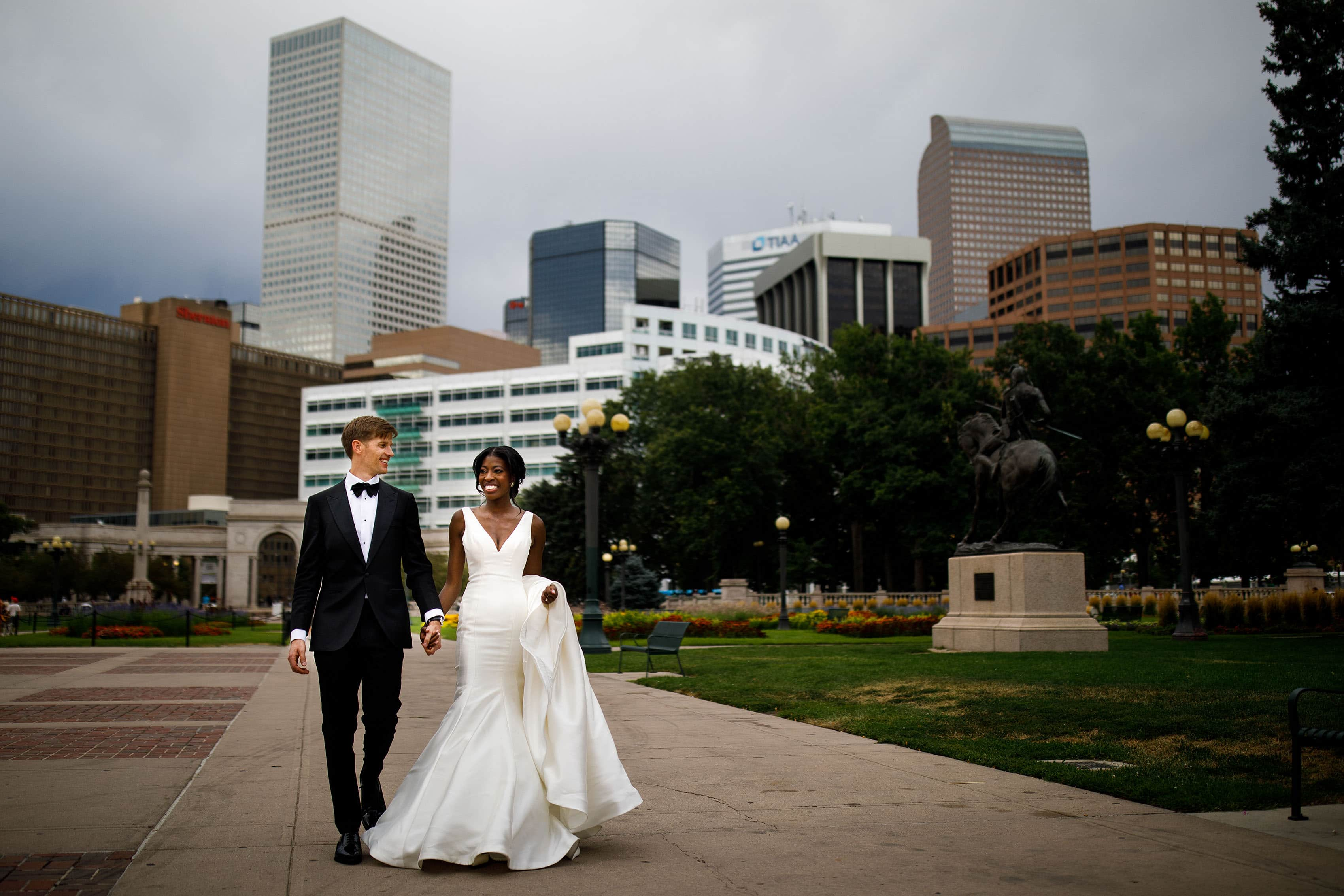 The bride and groom walk in Denver's Civic Center Park on their wedding day