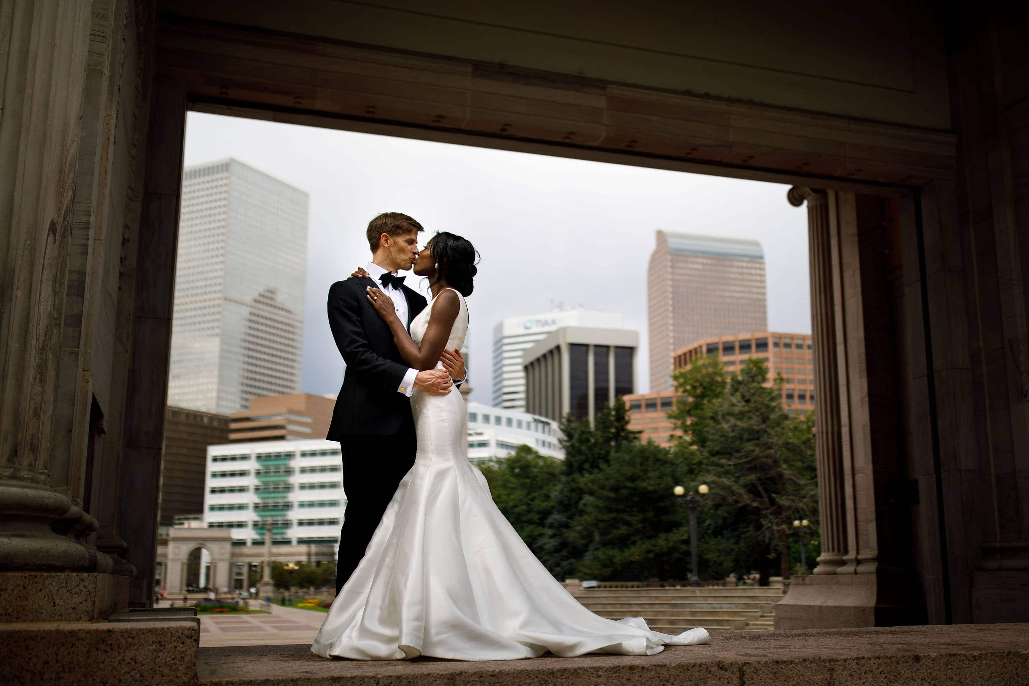 The couple kiss in the Greek ampatheatre at Denver's Civic Center Park on their wedding day