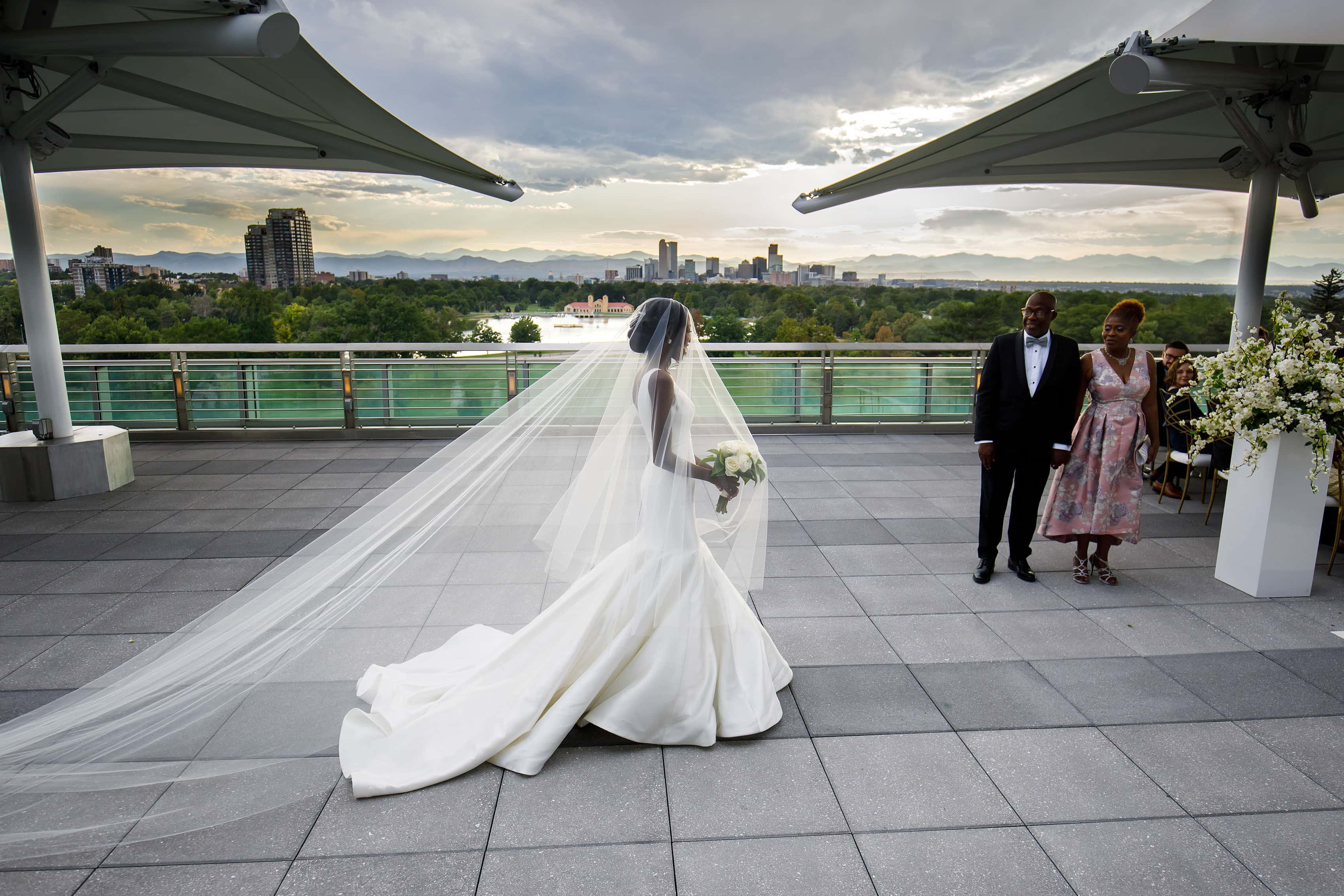 The bride walks down the aisle on the rooftop at the Denver Museum of Nature and Science during her wedding