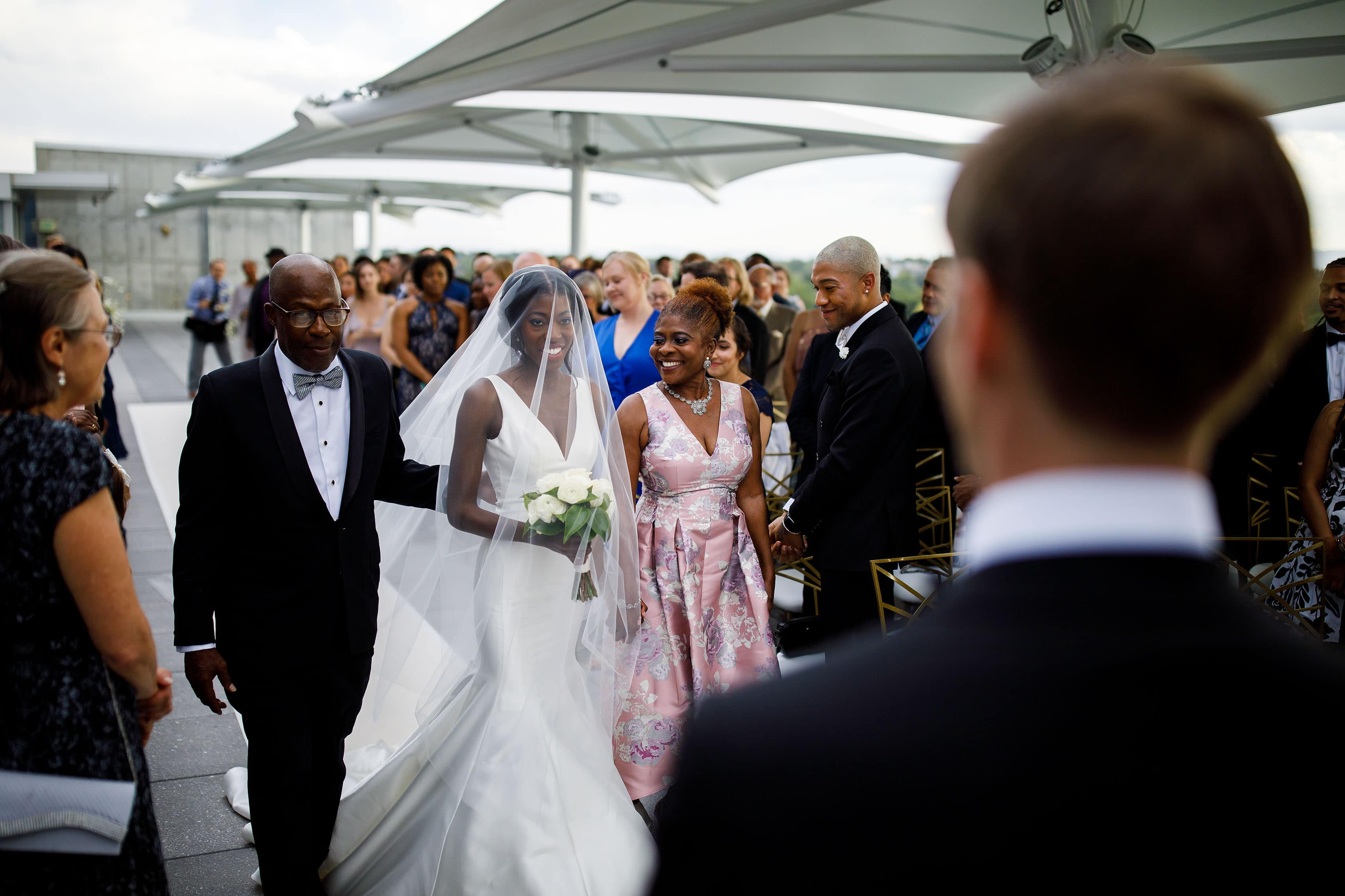 Ewo walks down the aisle with her parents on the rooftop at the Denver Museum of Nature and Science