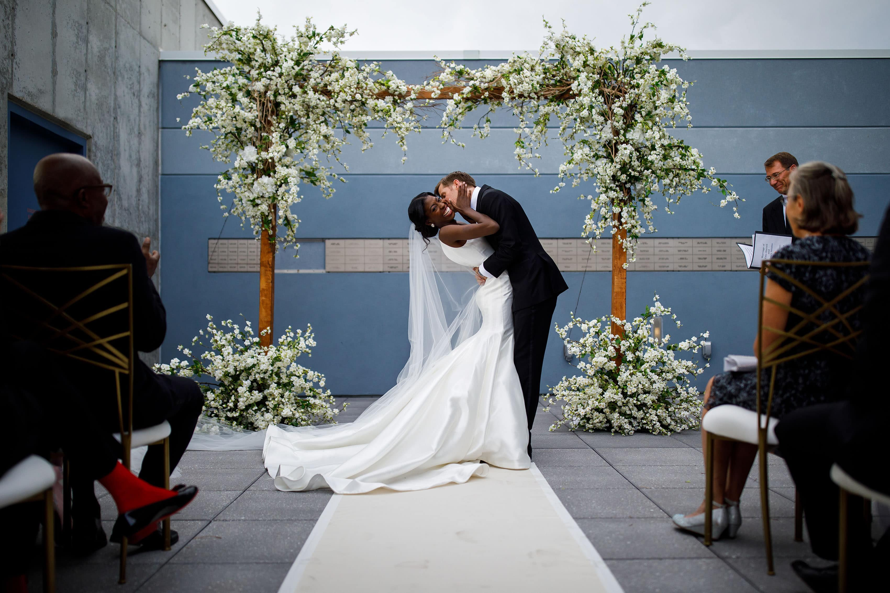 The newlyweds share a kiss during their rooftop ceremony at the Denver Museum of Nature and Science