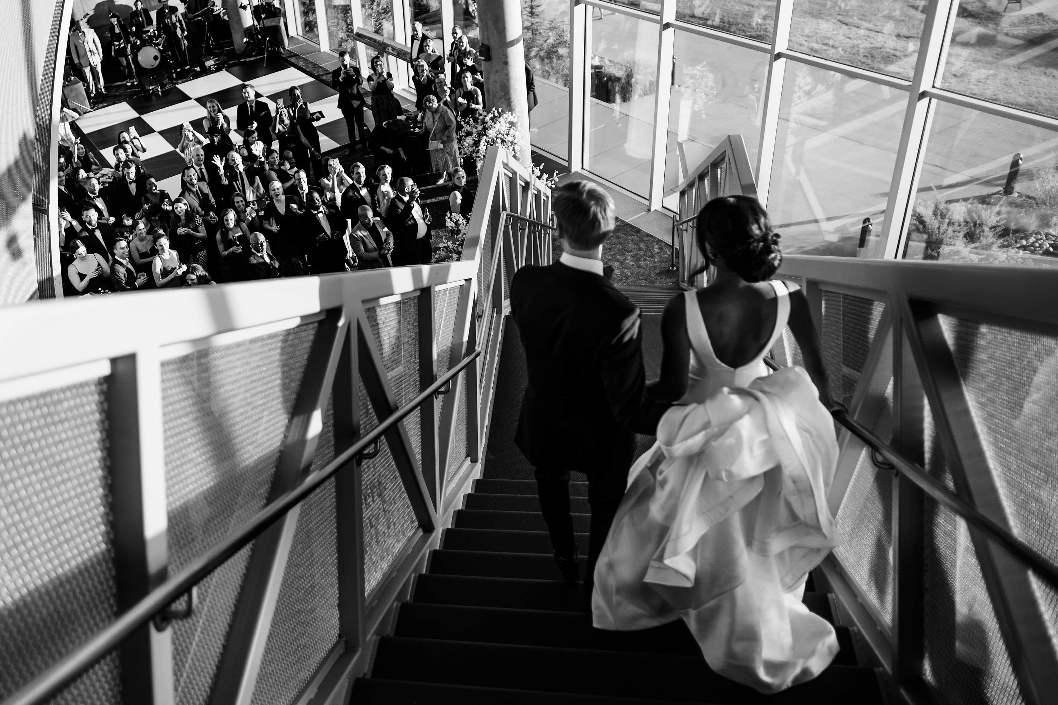 Bride and groom walk down the stairs in the grand atrium at the Denver Museum of Nature and Science