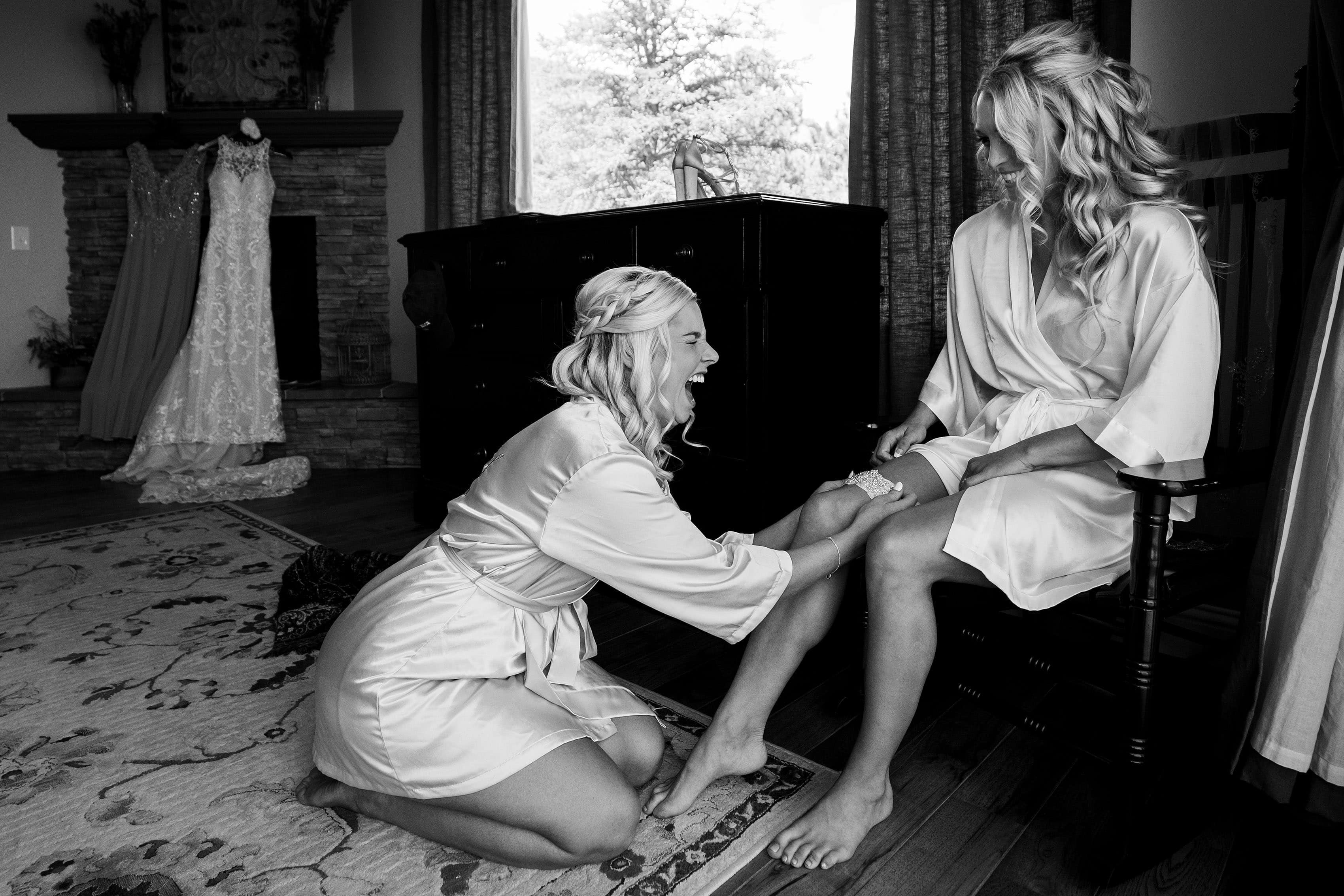 The bride and the maid of honor share a laugh before her Catholic Colorado Springs wedding
