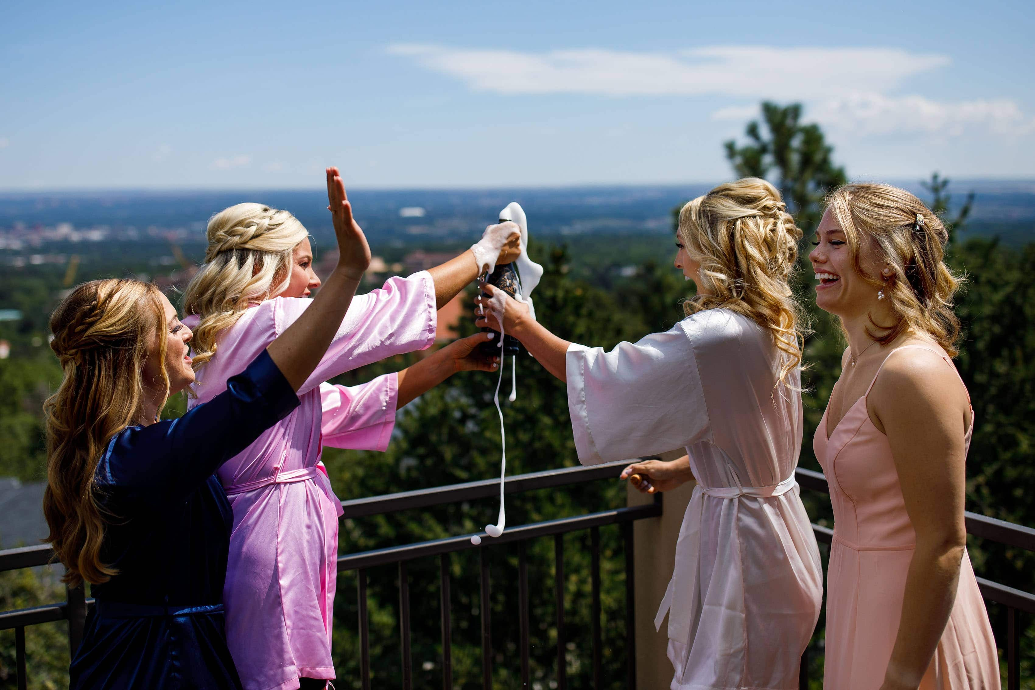 The bride and bridesmaids pop a bottle of champagne